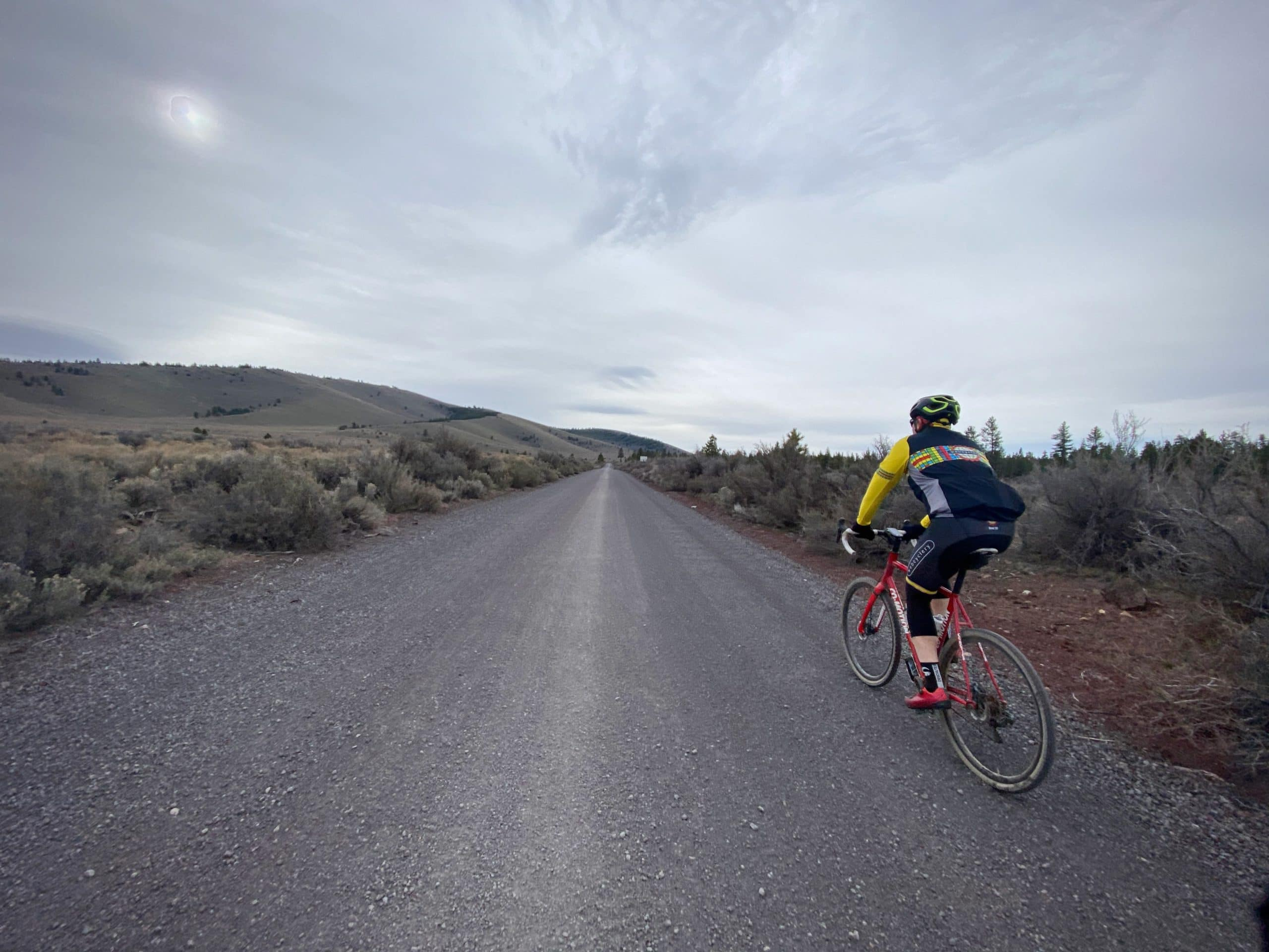 Cyclist riding gray gravel road in the Millican valley near Bend, Oregon.