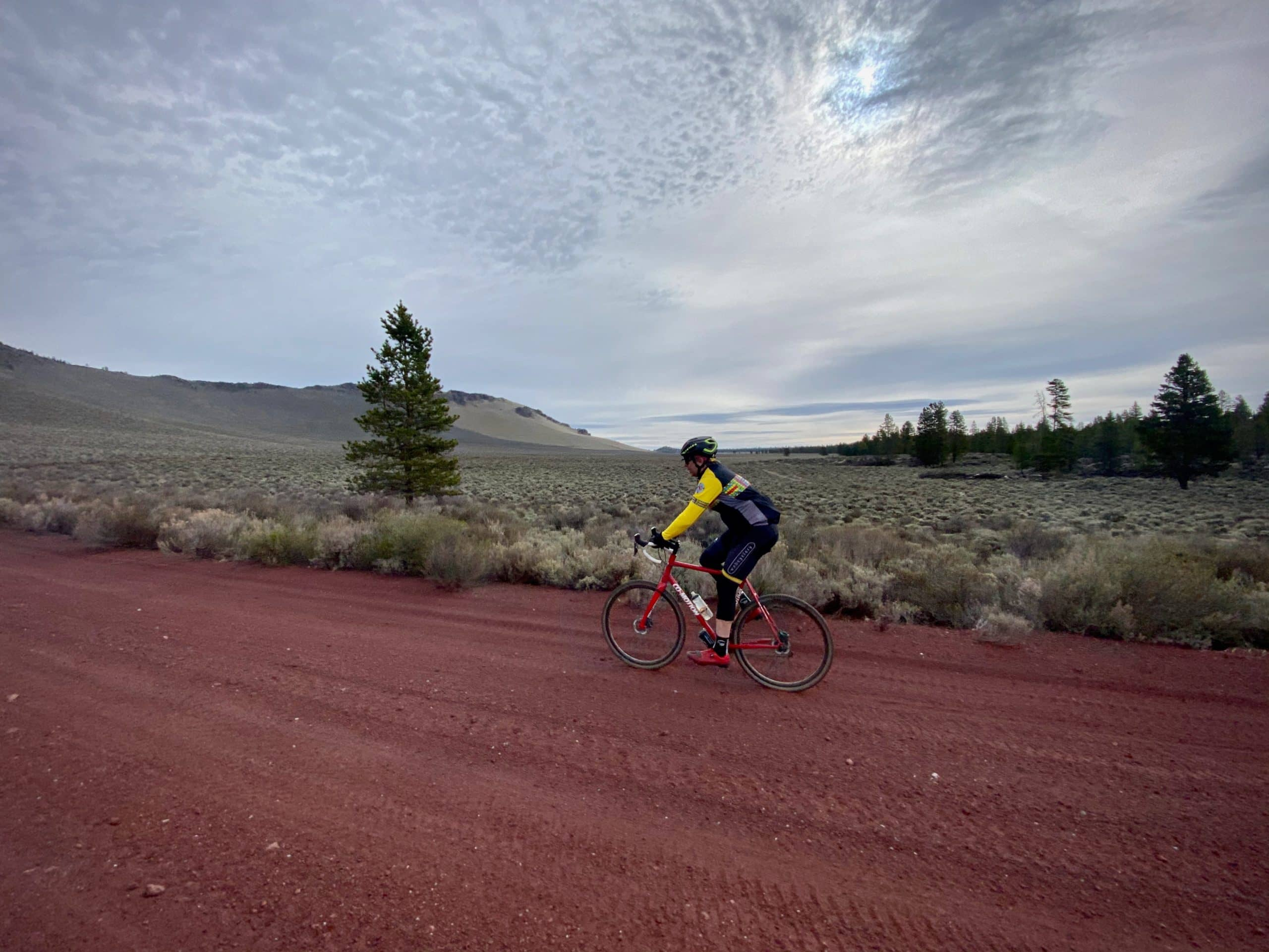 Gravel cyclist on red cinder road with Kotzman basin in the distance. Near Bend, OR.