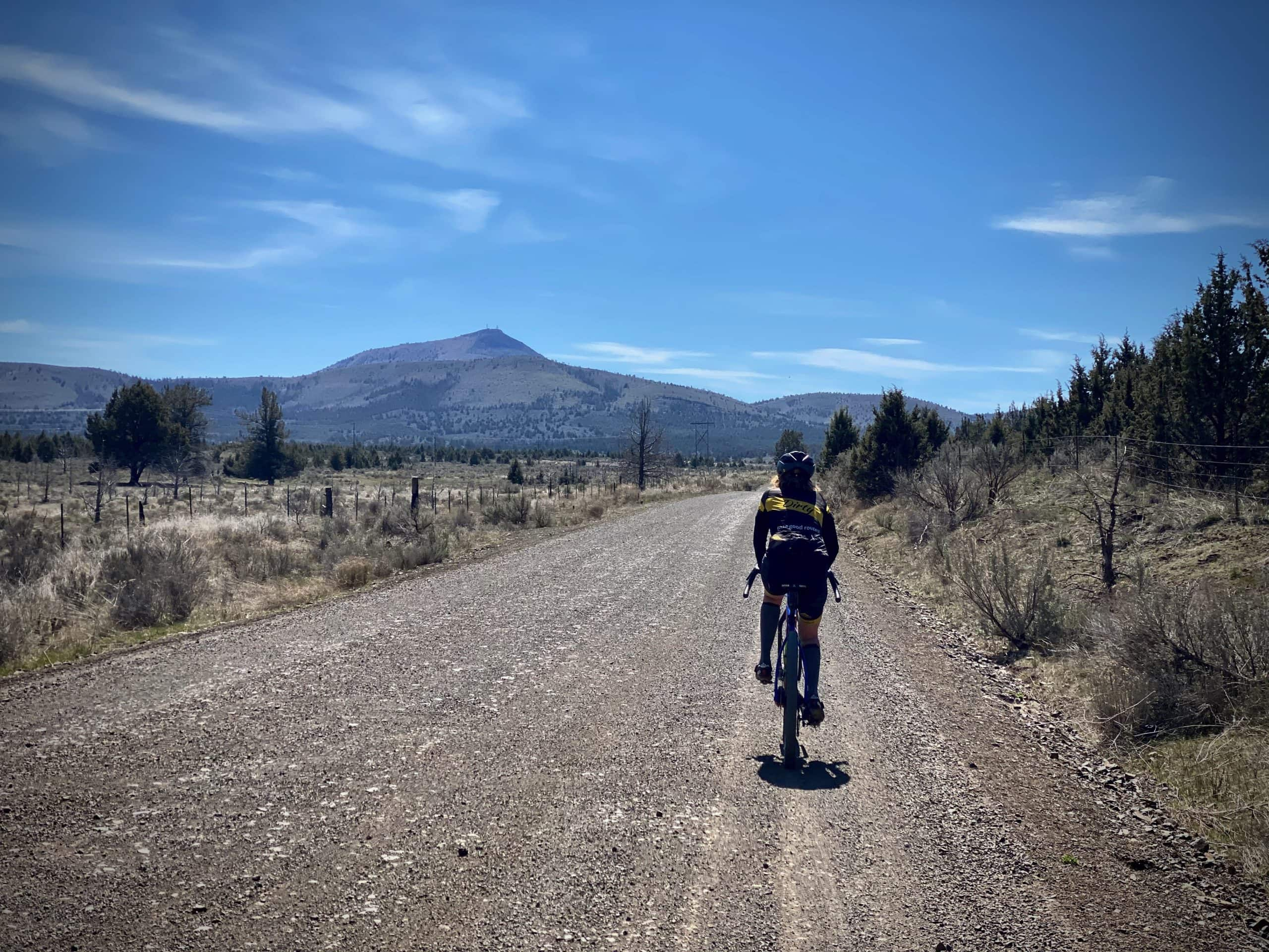 Cyclist on gravel road with Gray Butte in the distance. Near Smith Rock state park in Oregon.
