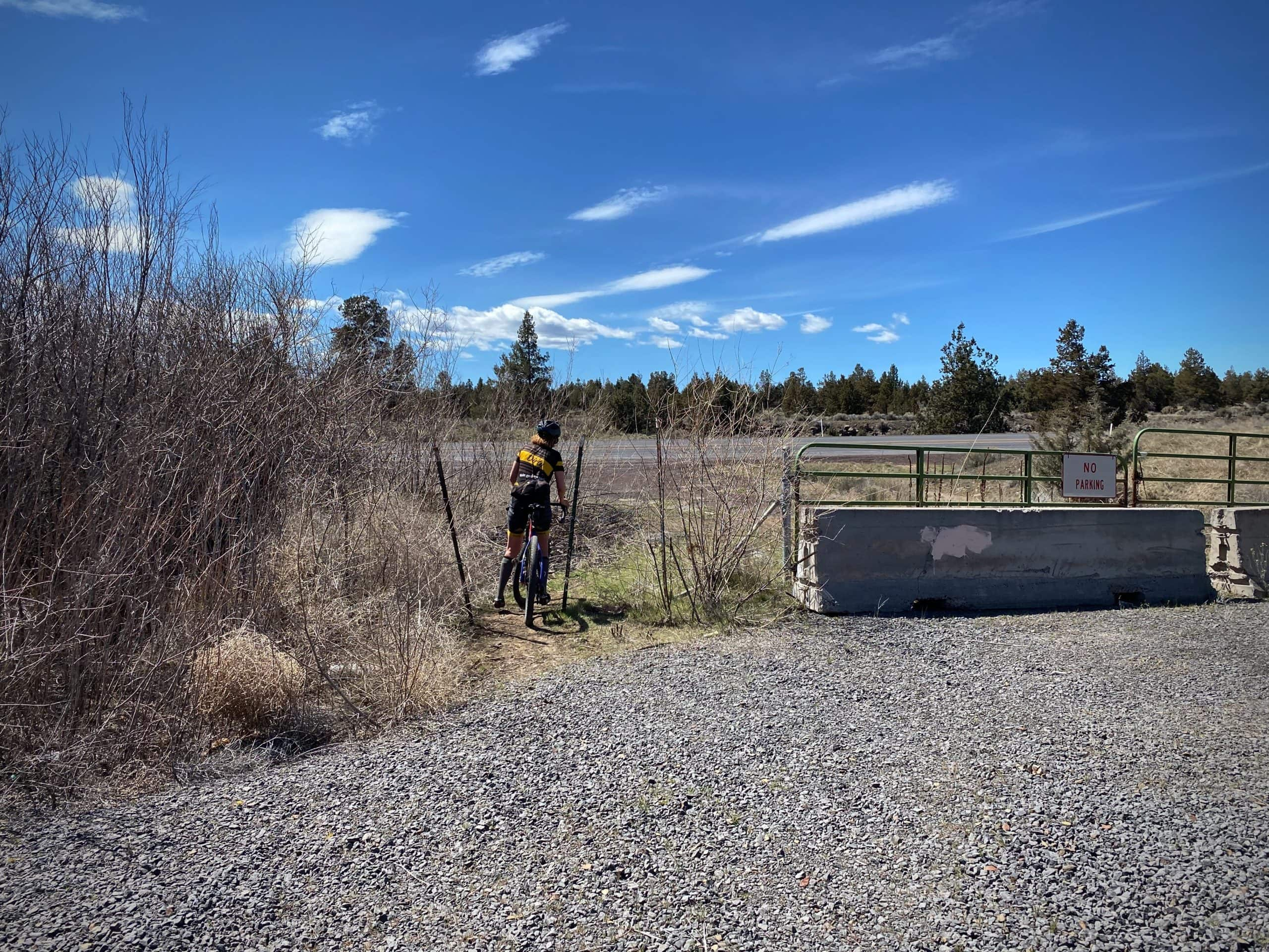 Cyclist crossing through gate between Culver highway and the Crooked River (High) bridge.