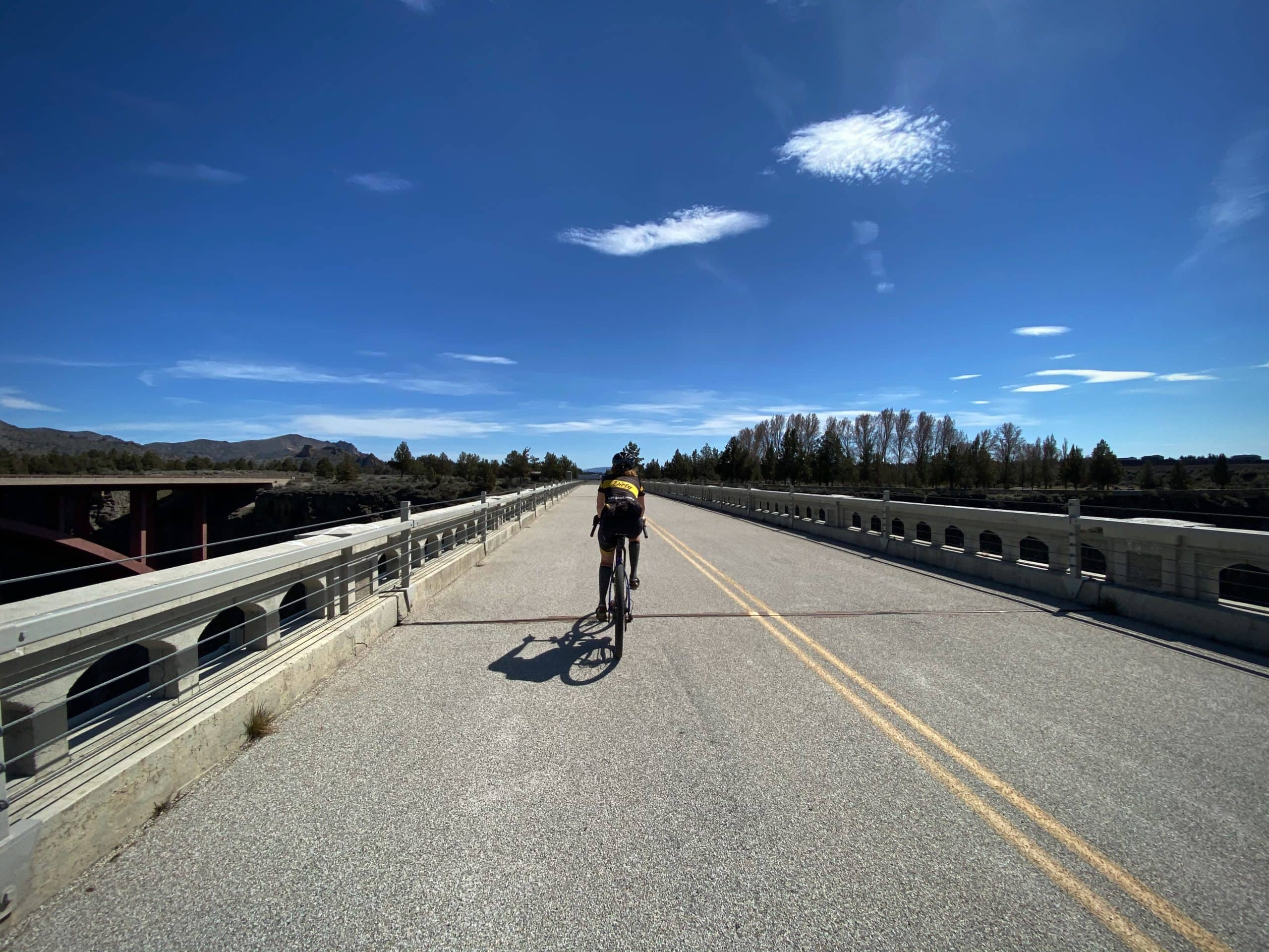 Cyclist riding across the Crooked River (High) bridge.