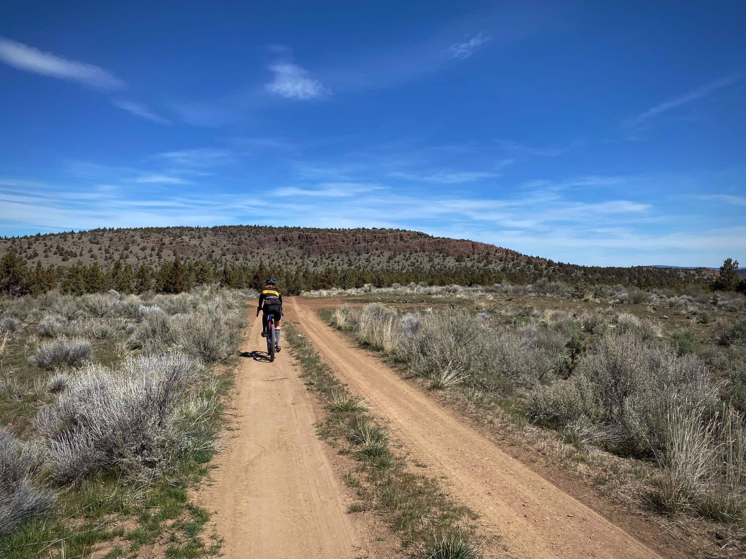 Cyclist on dirt road in Crooked River National Grassland.