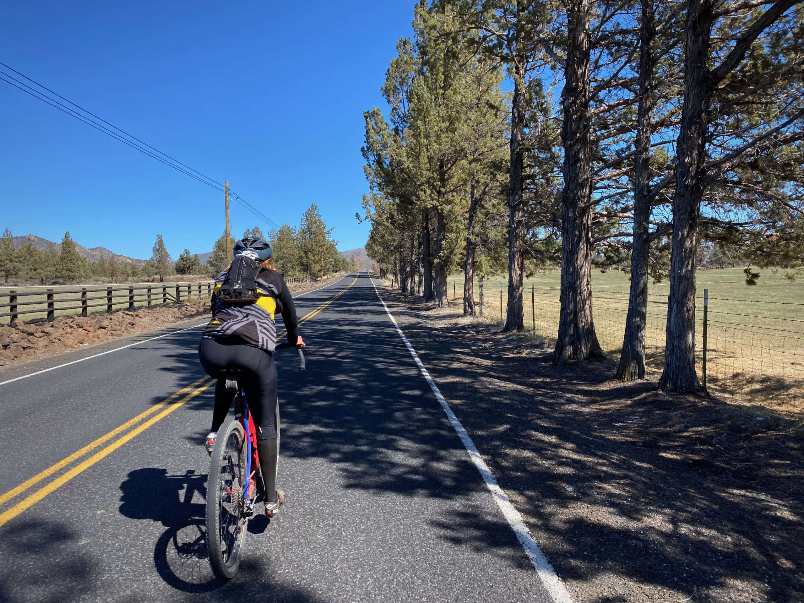Cyclist on paved roads leading out from Terrebonne, Oregon.