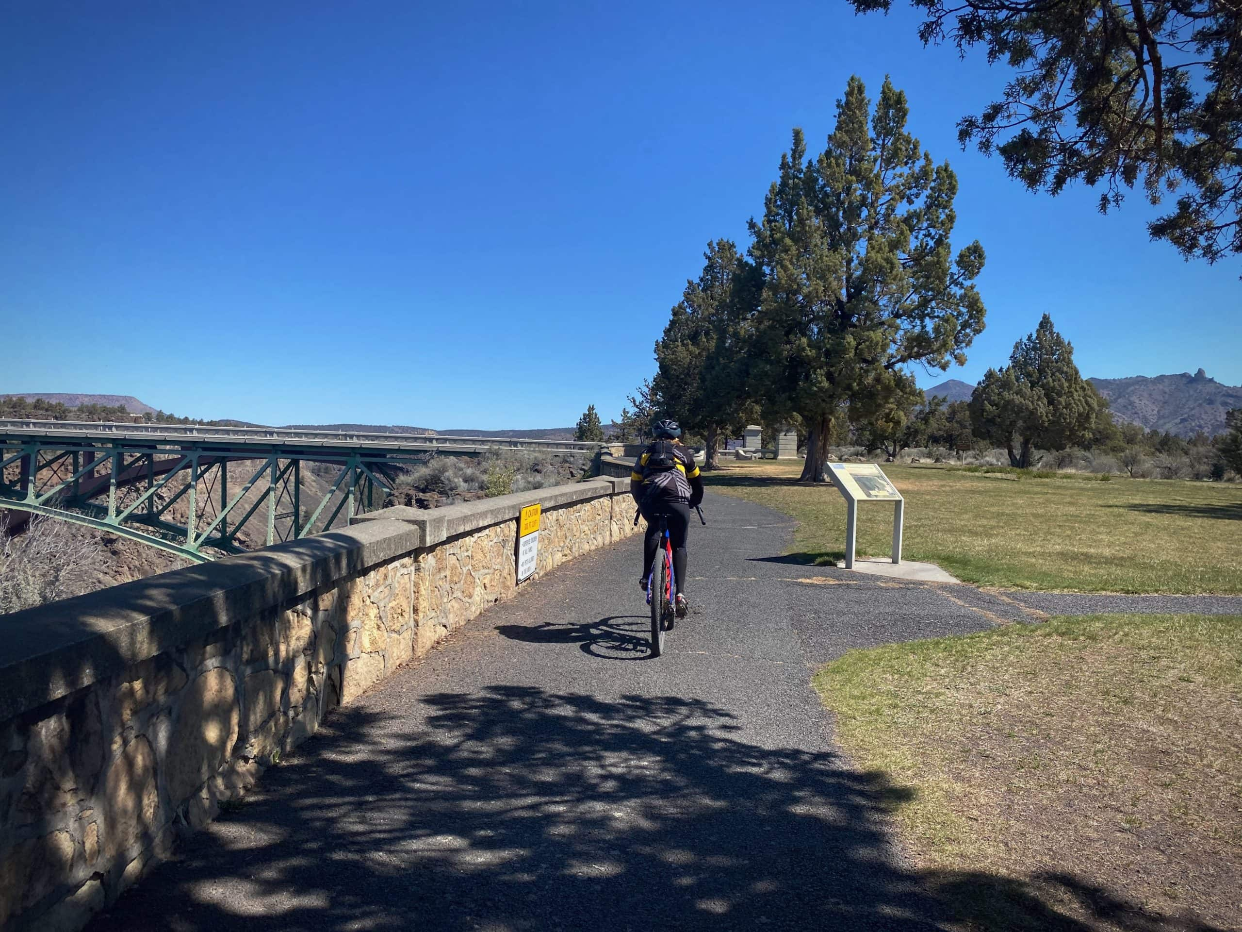 Cyclist on the paved path at the Crooked River gorge at the Peter Skene Ogden State Scenic viewpoint.