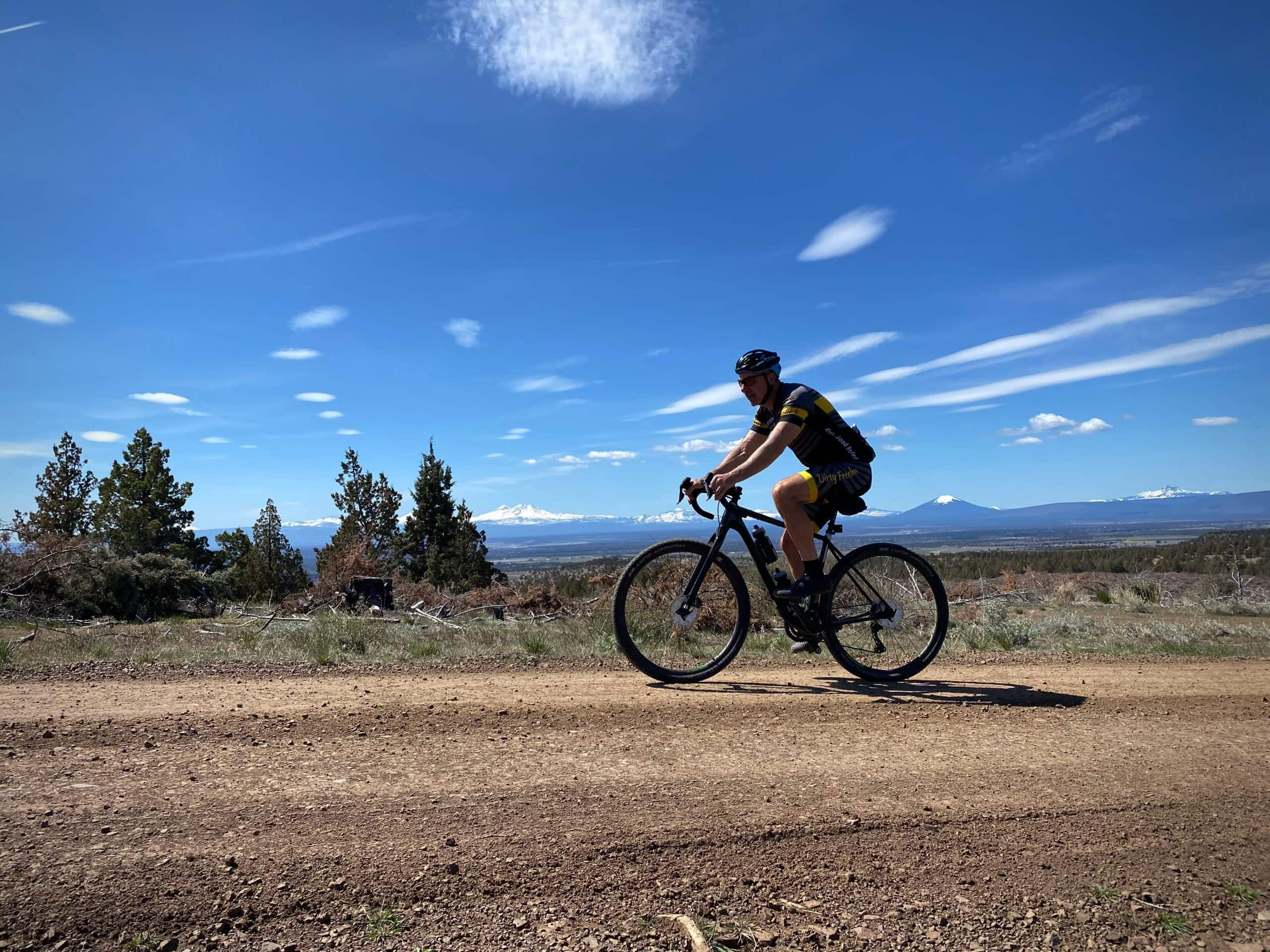 Gravel cyclist on forest service road in the National Grassland with views of the Cascade mountains in Central Oregon.