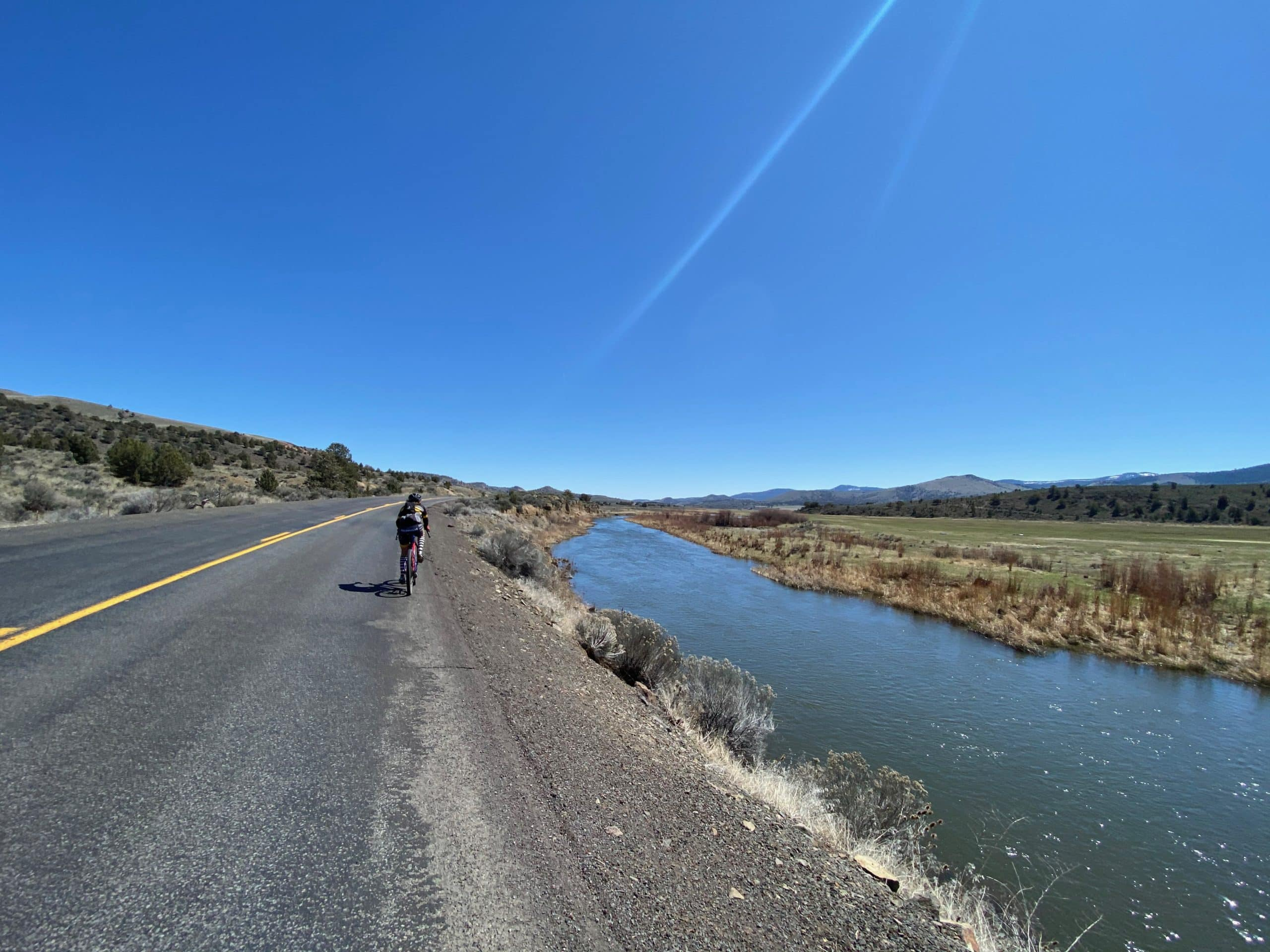 Cyclist riding next to Crooked River just outside of Post, Oregon.