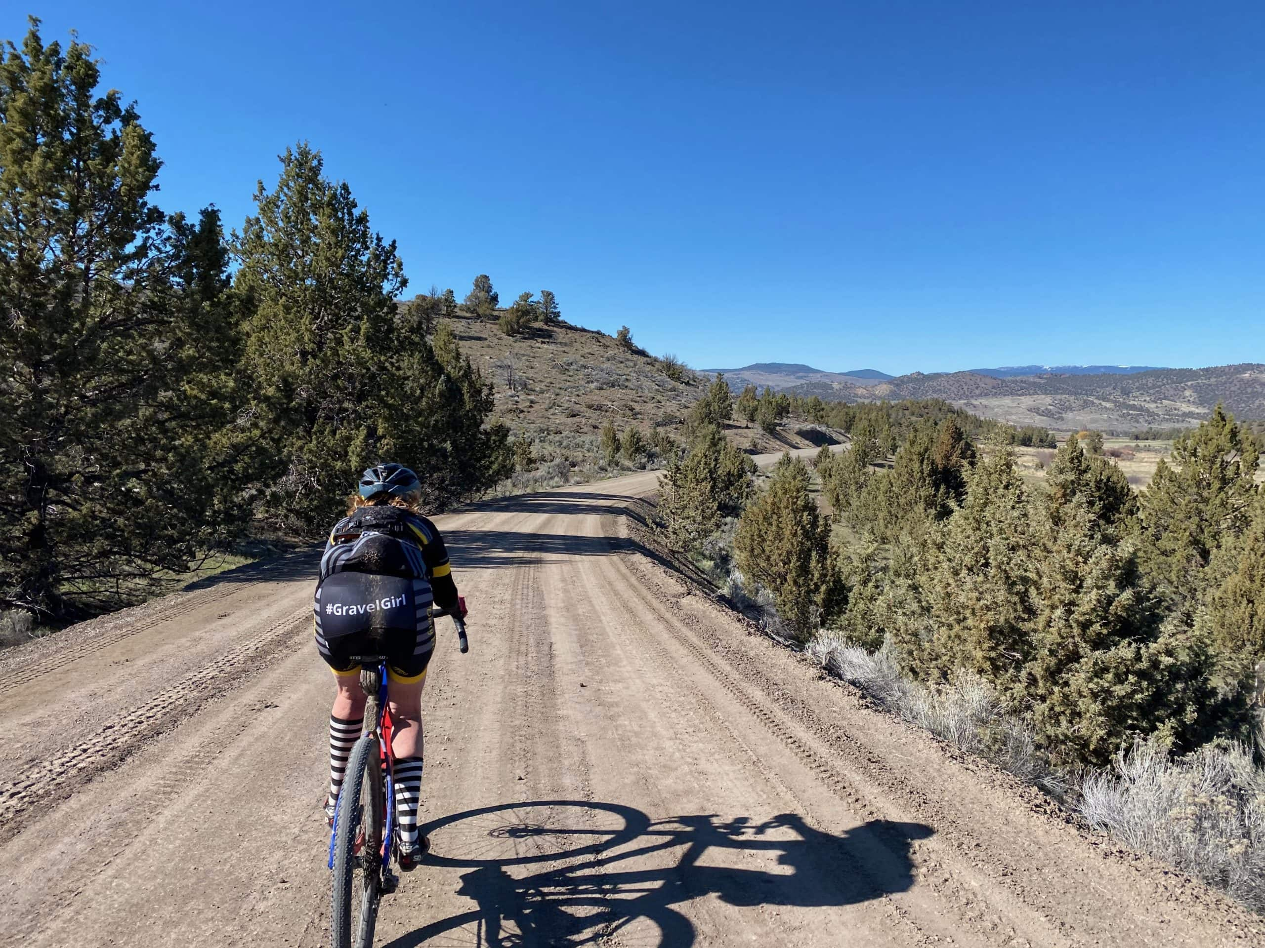 Woman gravel cyclist descending towards the Crooked River near Post, OR.