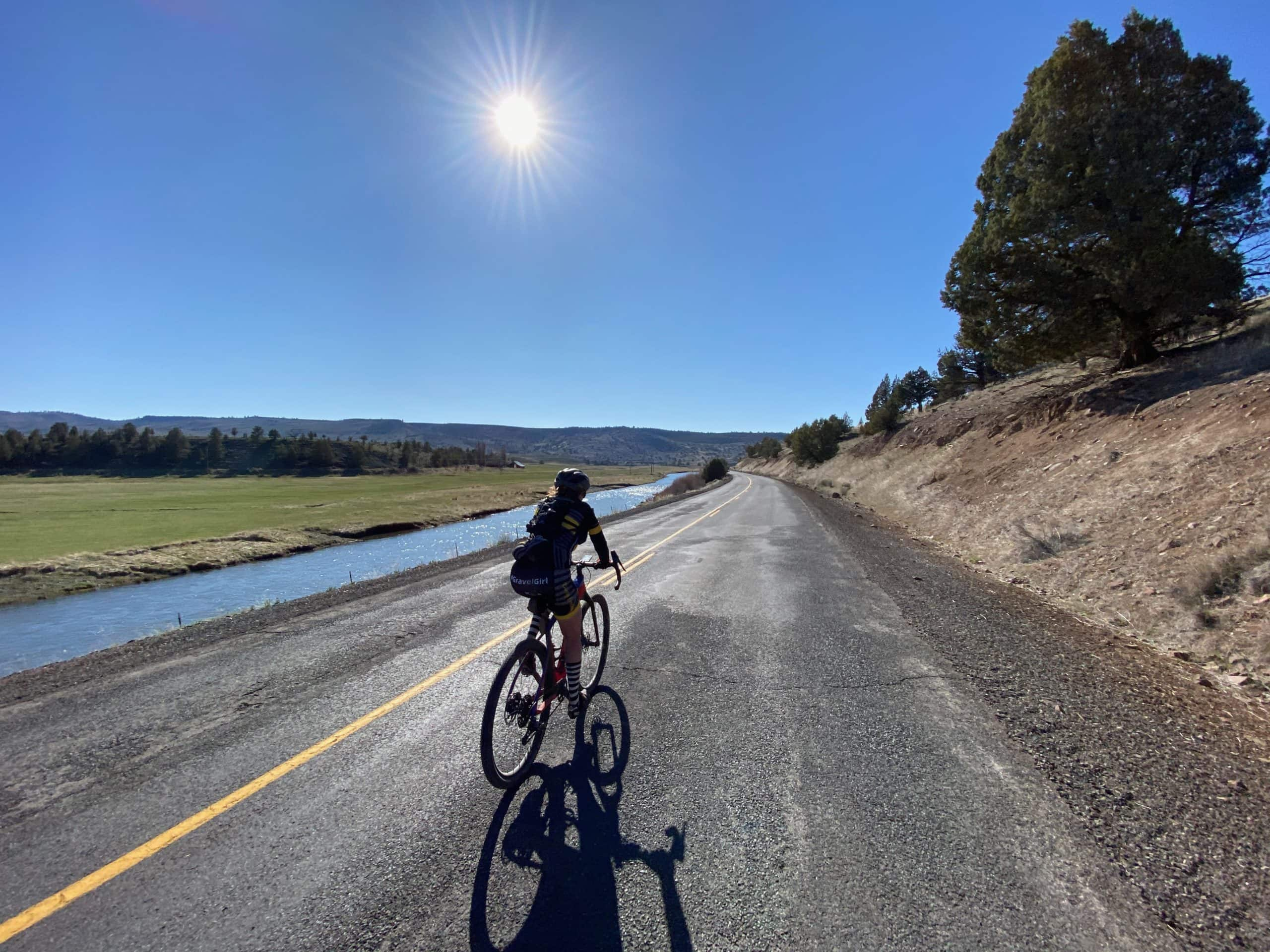Cyclist on Highway 380 near Post, Oregon with Crooked River in background.