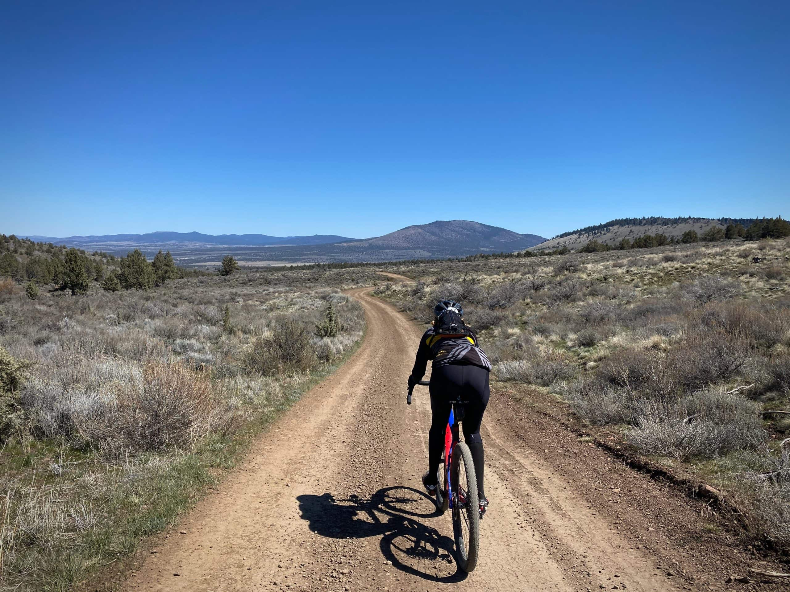 Cyclist on gravel road with Grizzly Mountain in the background. Near Prineville, Oregon.