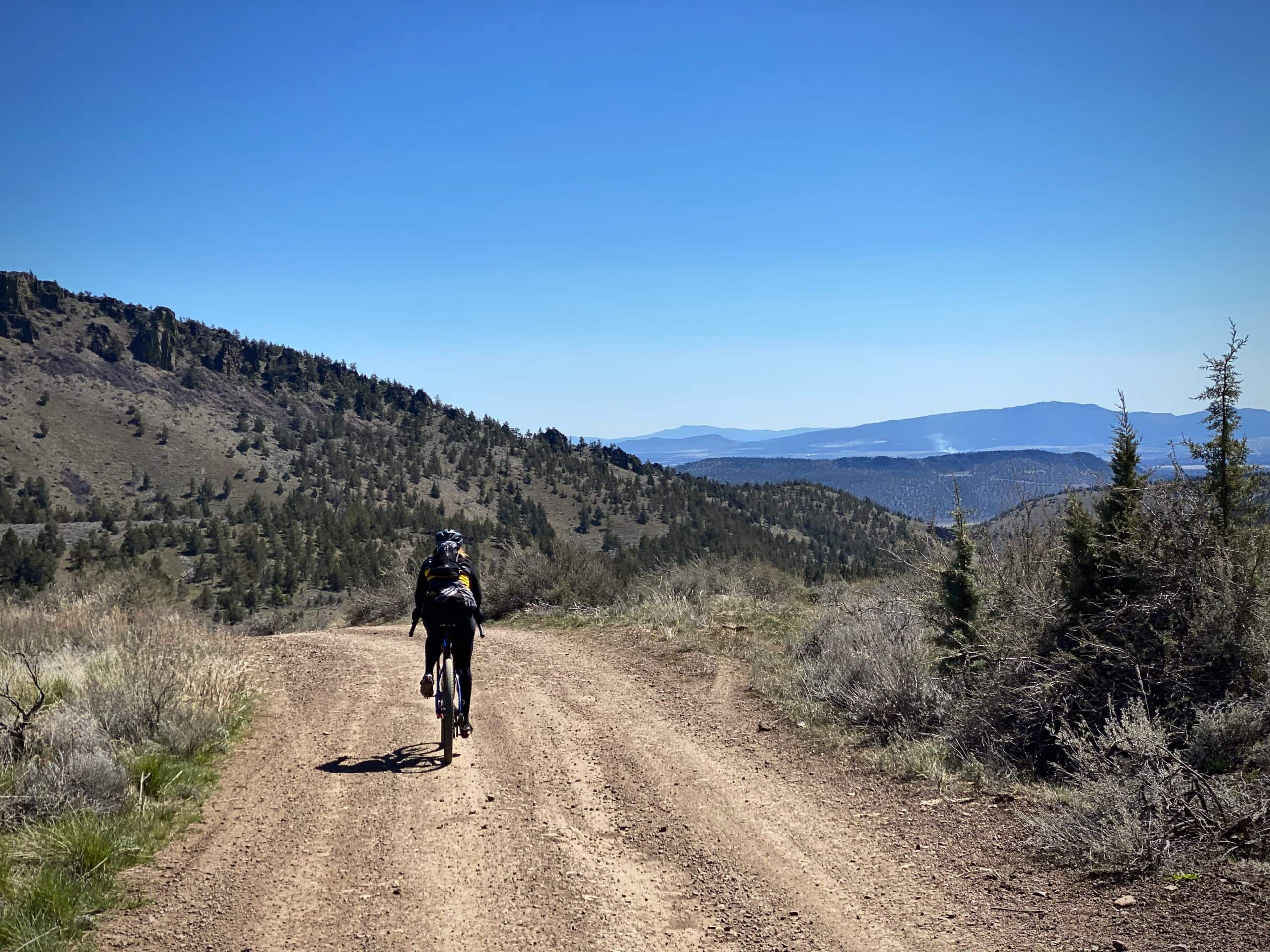 Gravel cyclist on dirt road in Crooked River National Grassland near Redmond, OR.