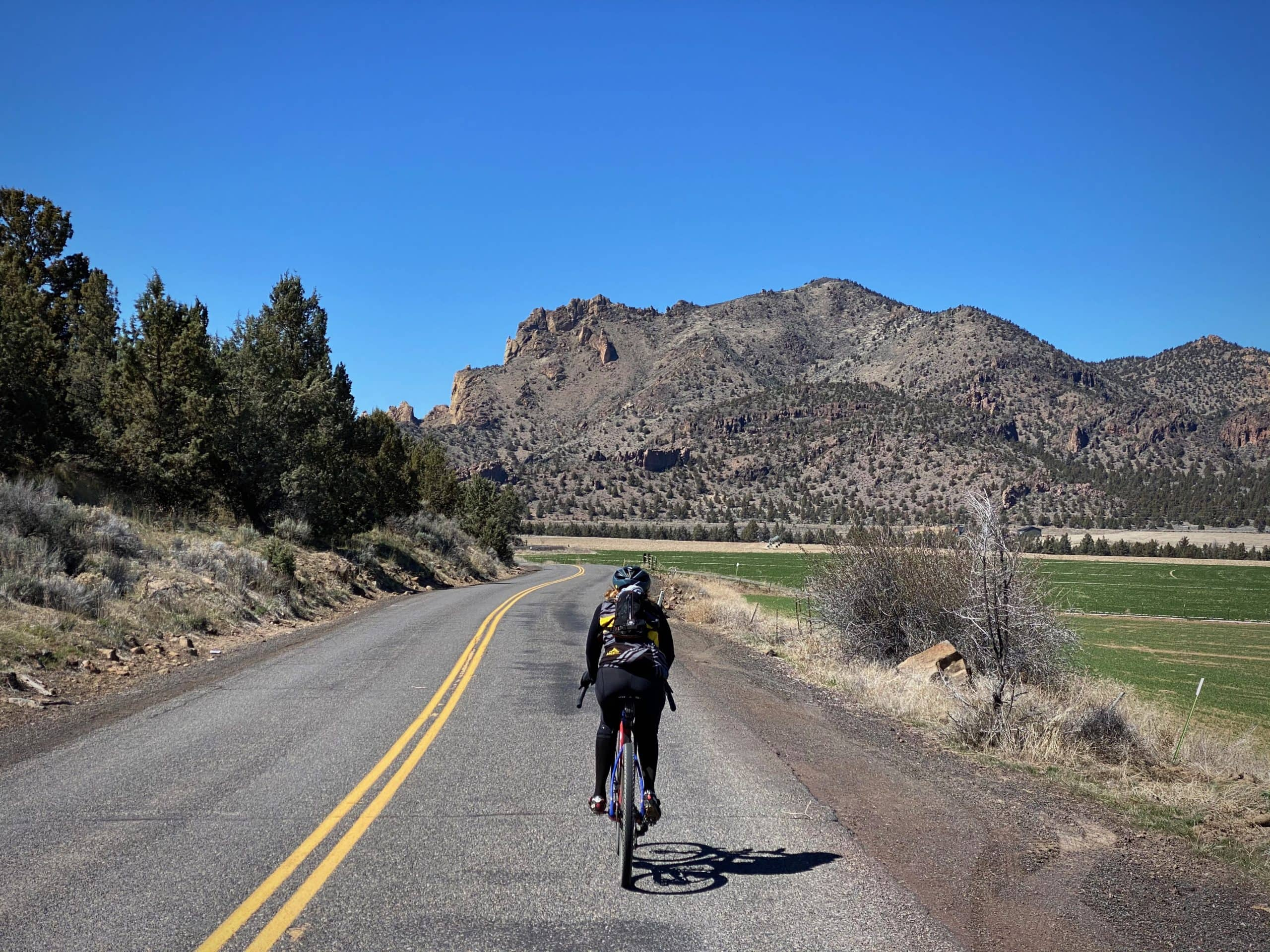 Cyclist riding a paved road with Smith Rock state park in the background. Terrebonne, Oregon.