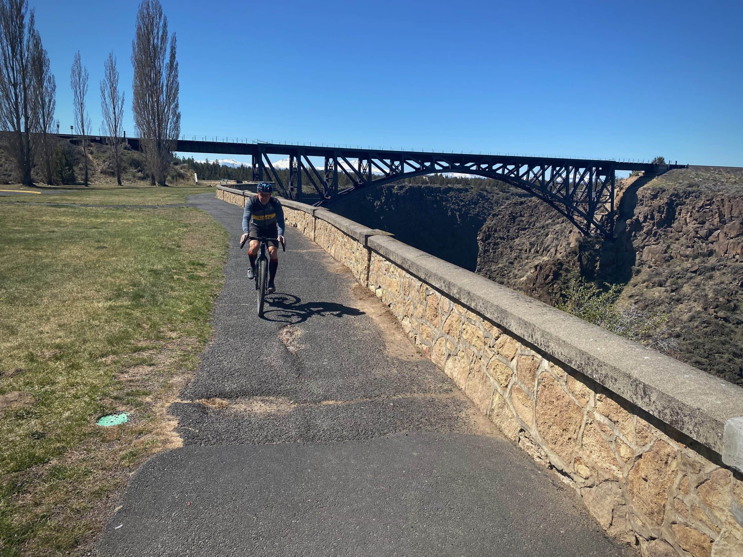 Cyclist riding paved path with the historic Oregon Trunk Rail Lineway bridge in the background.