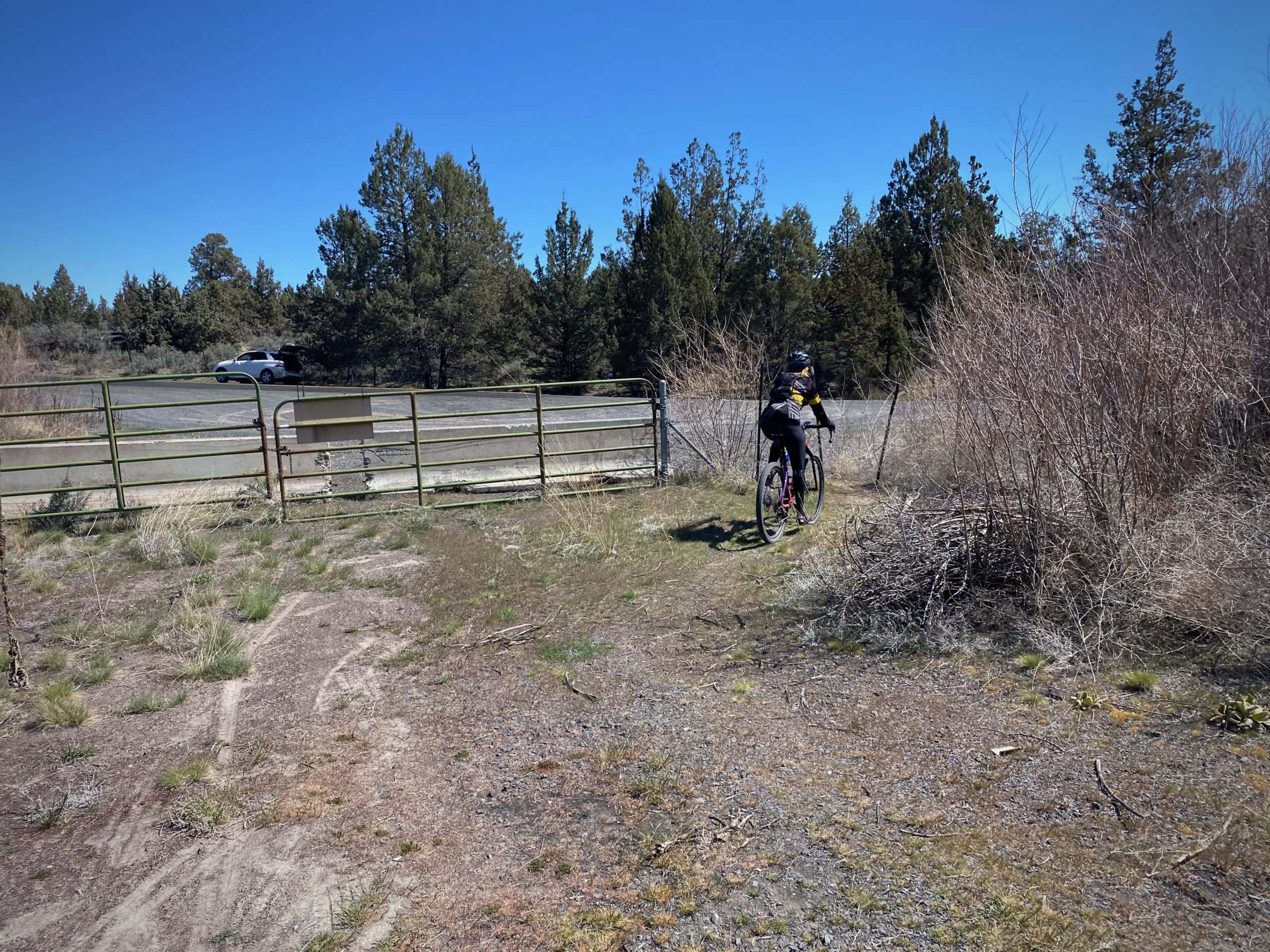 Cyclist passing through fence connecting the Culver Highway to Highway 87 near Madras, Oregon.