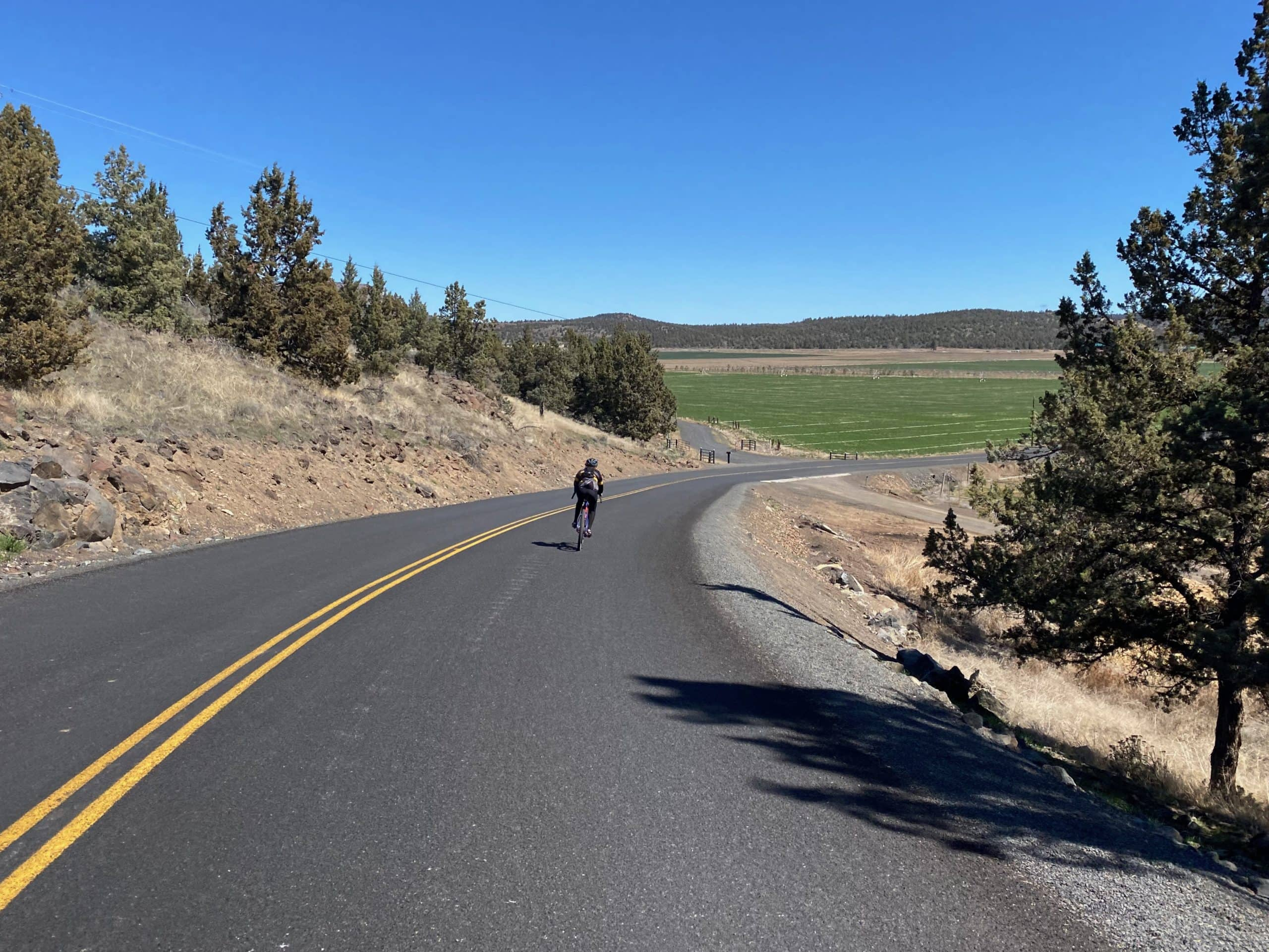 Cyclist on road dropping into McPheeters Turf farm near Smith Rock state park in Oregon.