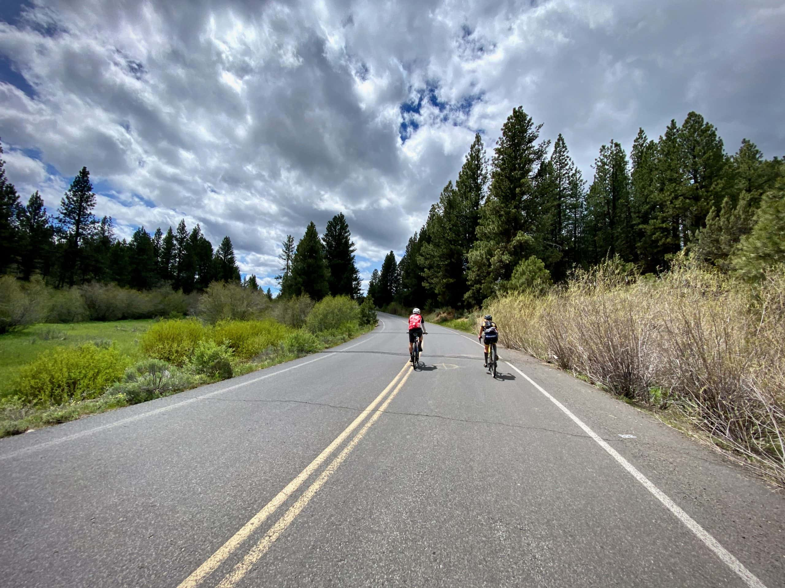 Cyclists passing over creek near a high alpine prairie in the Ochoco National forest.