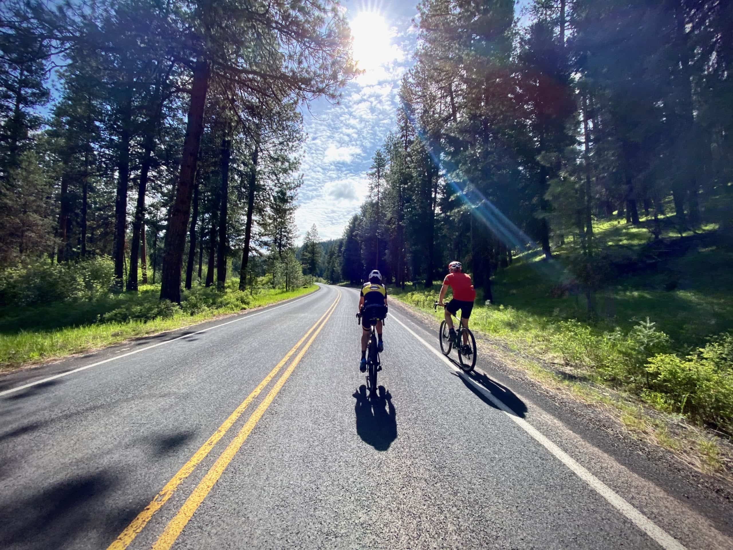 Cyclists riding away from old Ochoco Ranger station near Prineville, OR.
