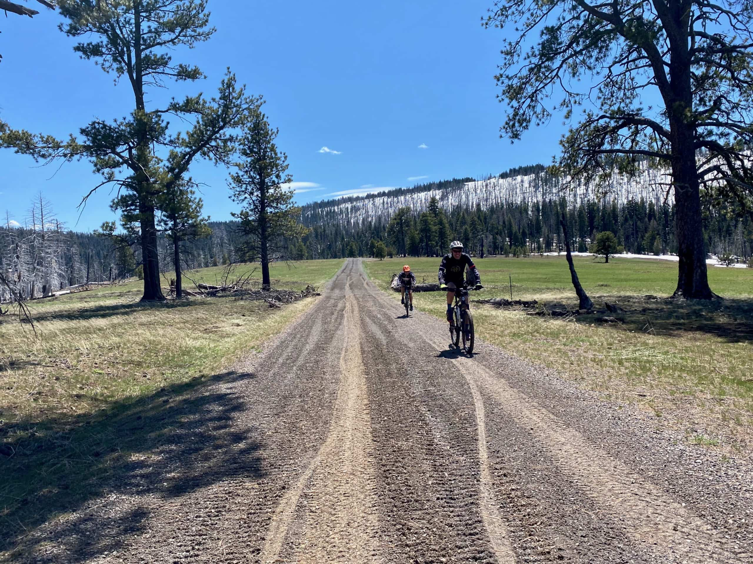 Cyclists on gravel road with Wolf mountain in the background near Ragar ranger station in Oregon.