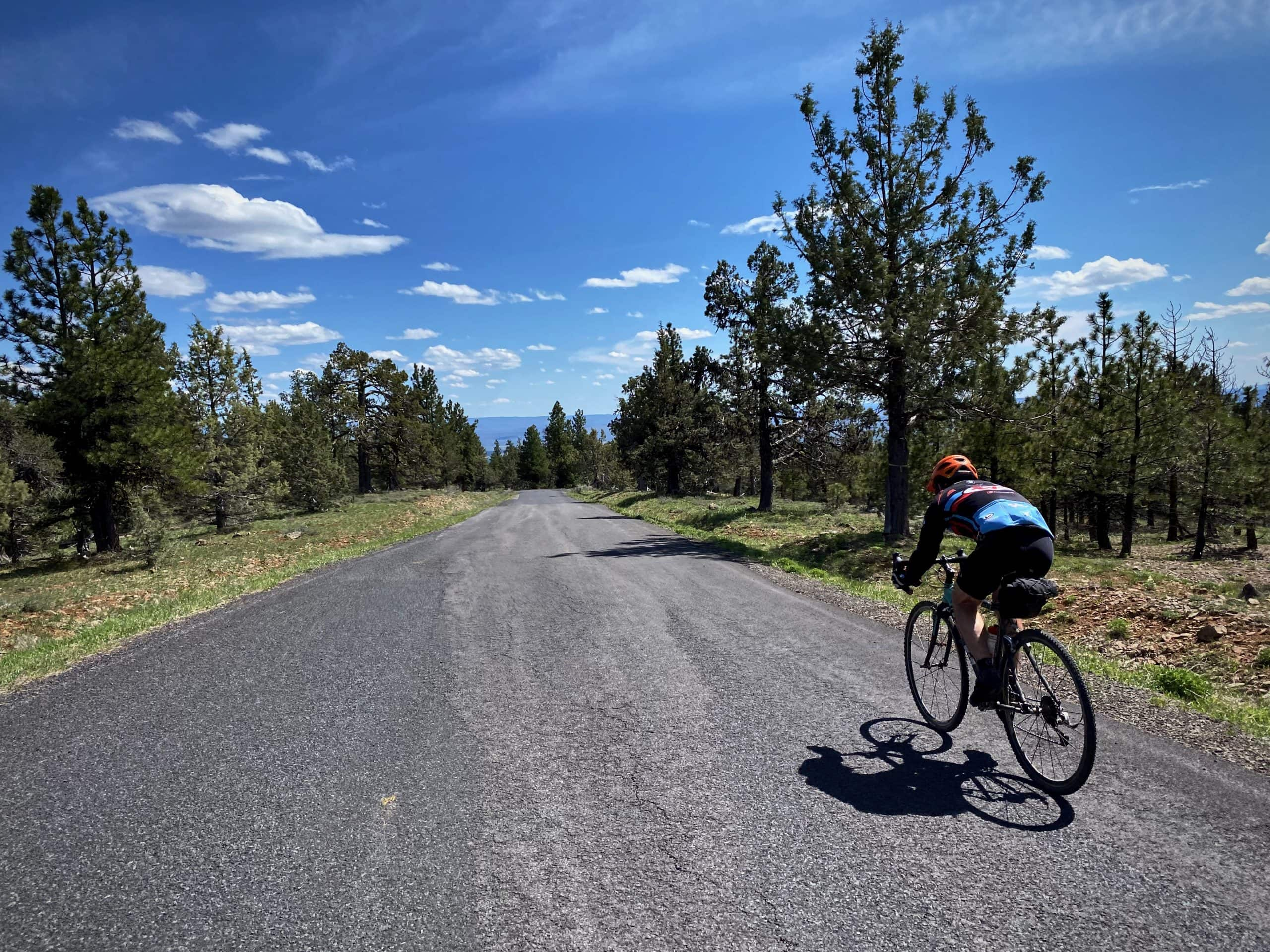 Cyclist beginning the paved descent on NF-42 in the Ochoco National forest near Paulina, OR.