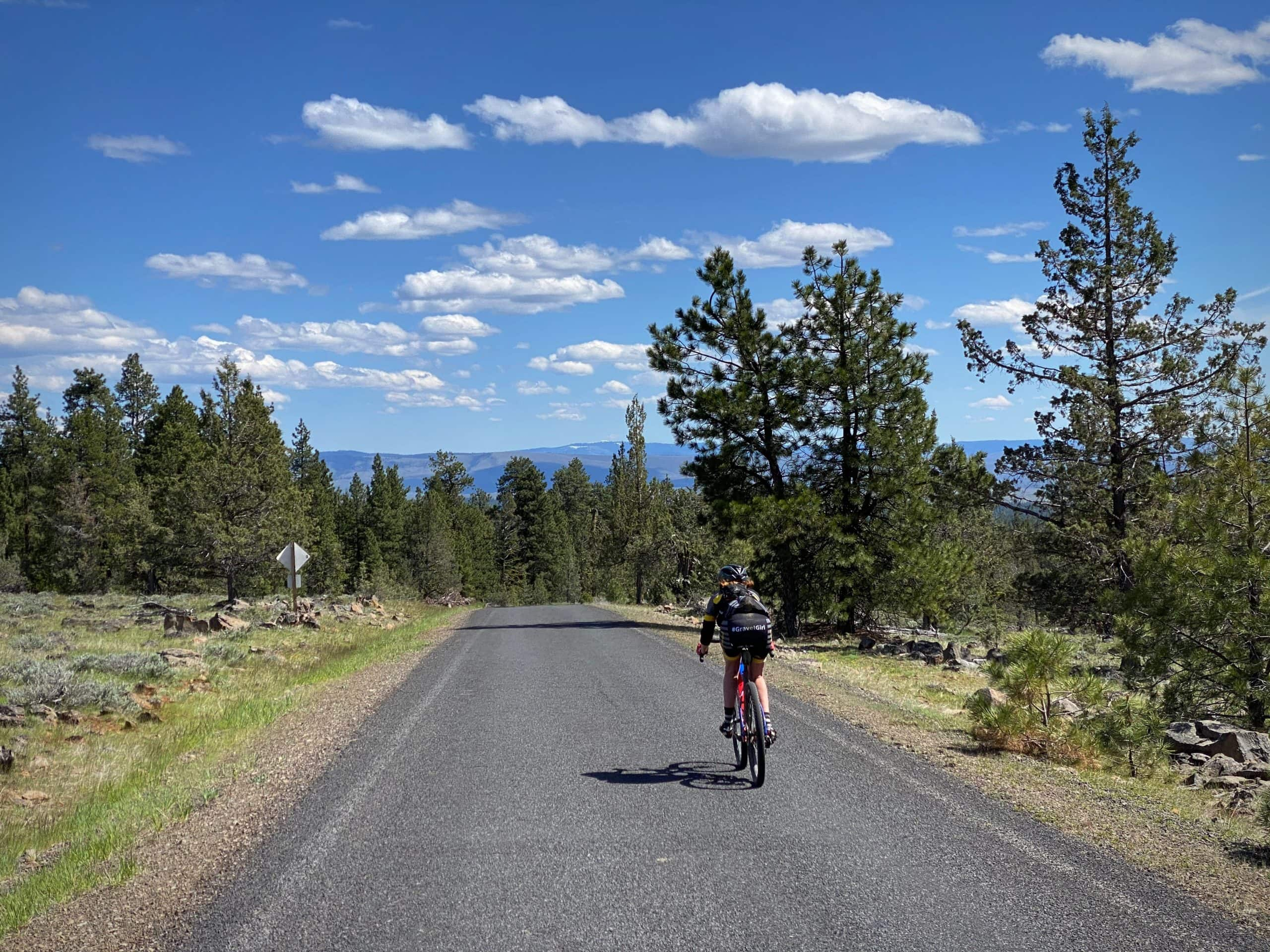 Woman bike rider on NF-42 downhill in the Ochoco mountains.