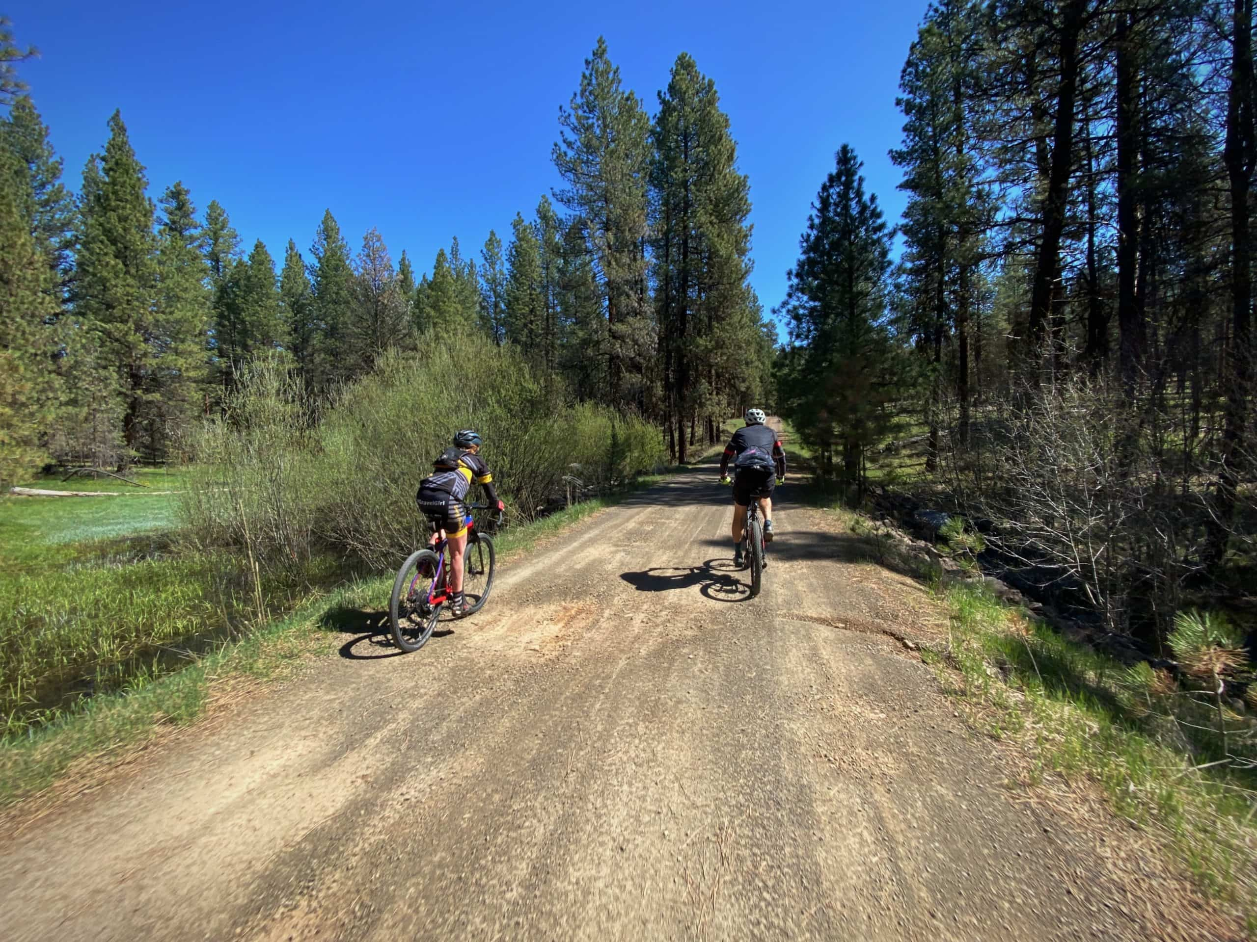 Two gravel cyclist on forest service road crossing over Sugar creek in Central Oregon.