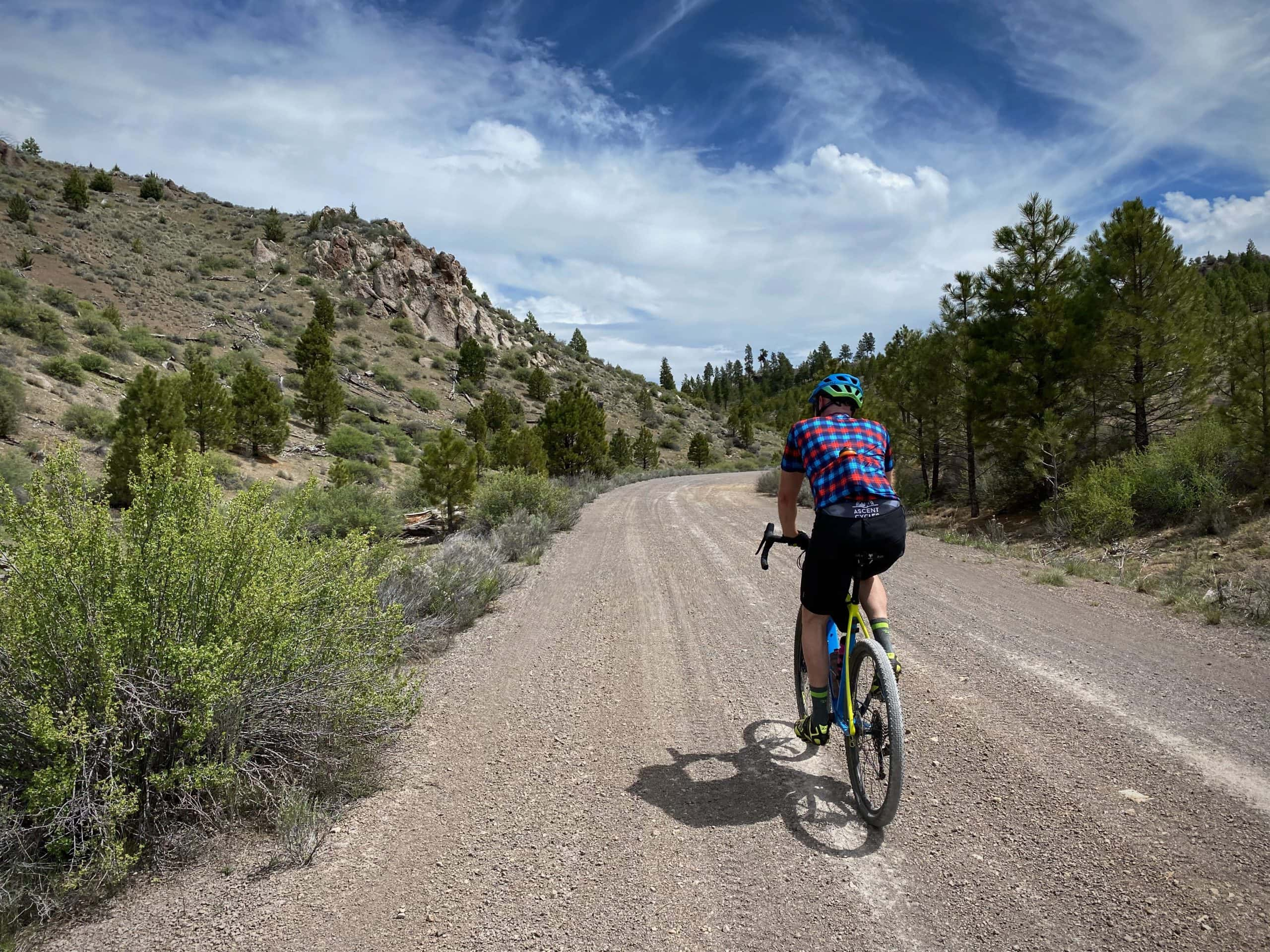 Cyclist on gravel road with limestone rock outcroppings near Burns, Oregon.