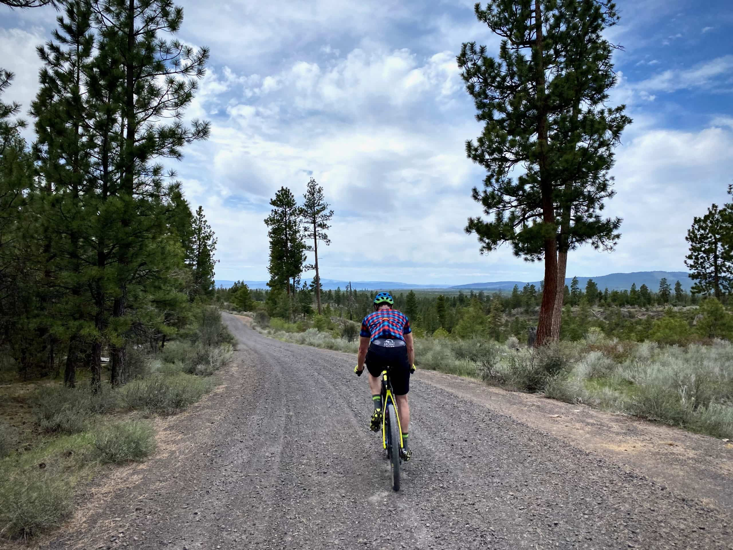 Cyclist on gravel road riding towards Dick Miller Canyon and Riley, Oregon.
