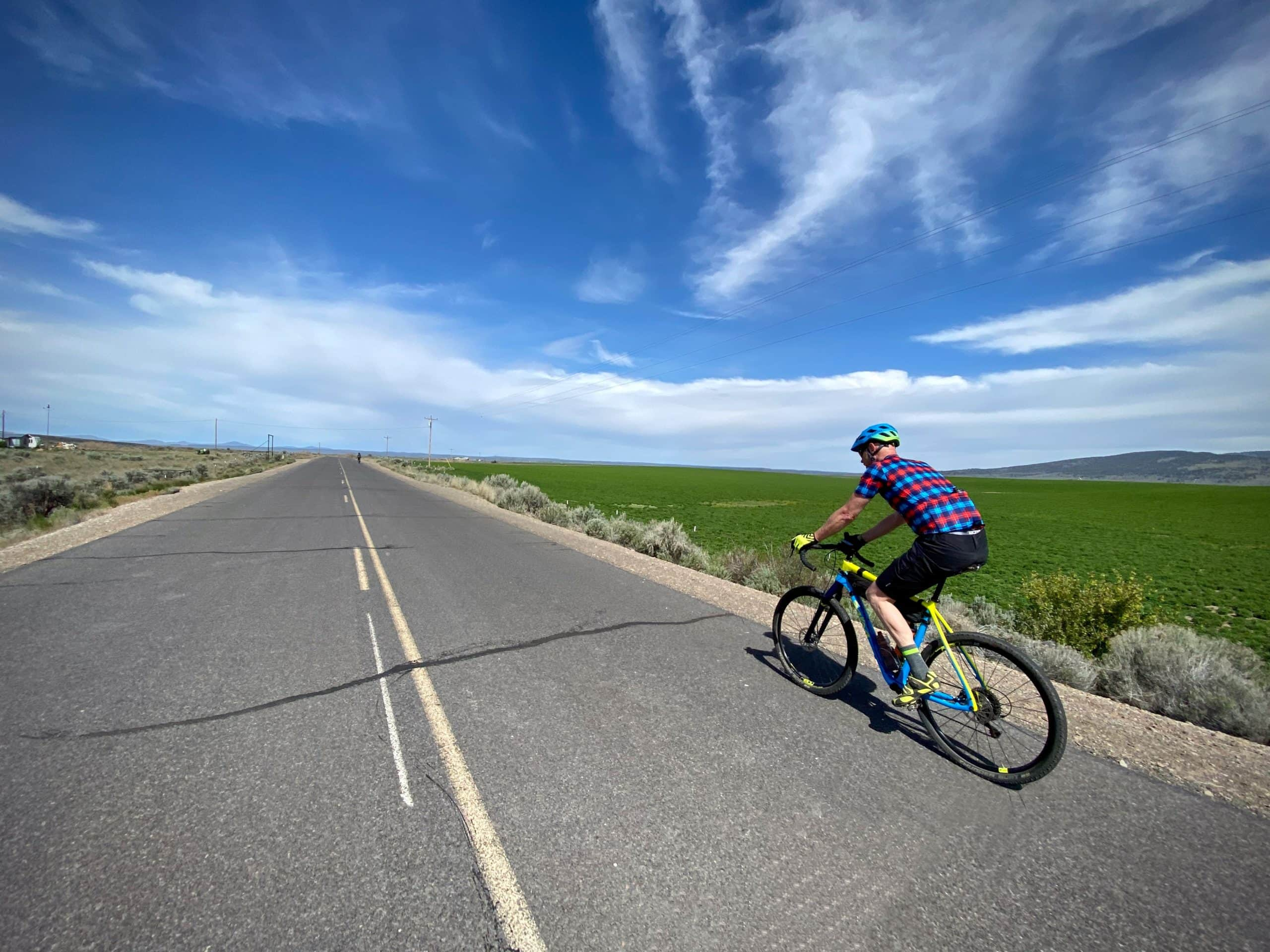 Cyclist leading out on Silver Creek road (paved) near Riley, OR.