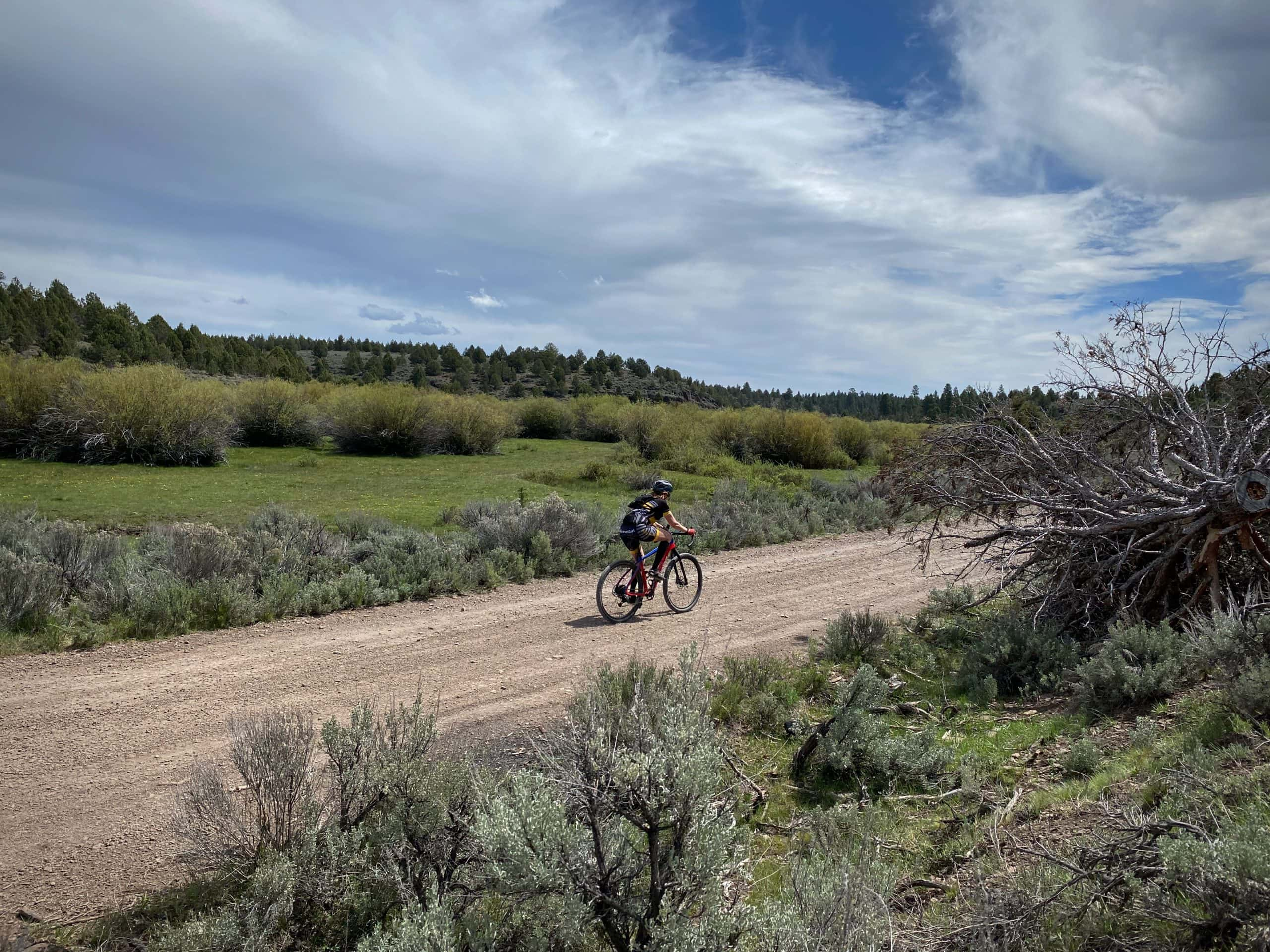 Cyclist riding gravel road with wetlands and Egypt Creek in the background.