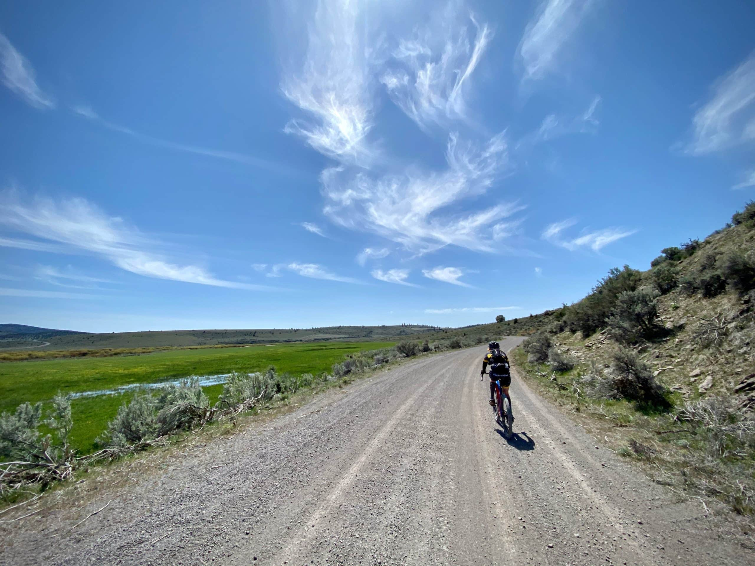 Gravel Cyclist riding on NF-45 past the wetlands of Silver Creek in Upper Valley near Riley, Oregon.