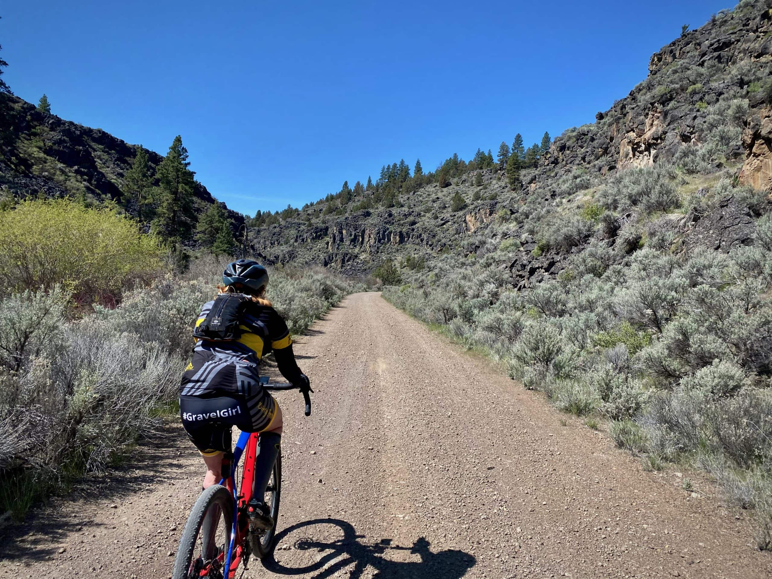 Woman gravel cyclist entering Silver Spring canyon on dirt road near Riley, OR.