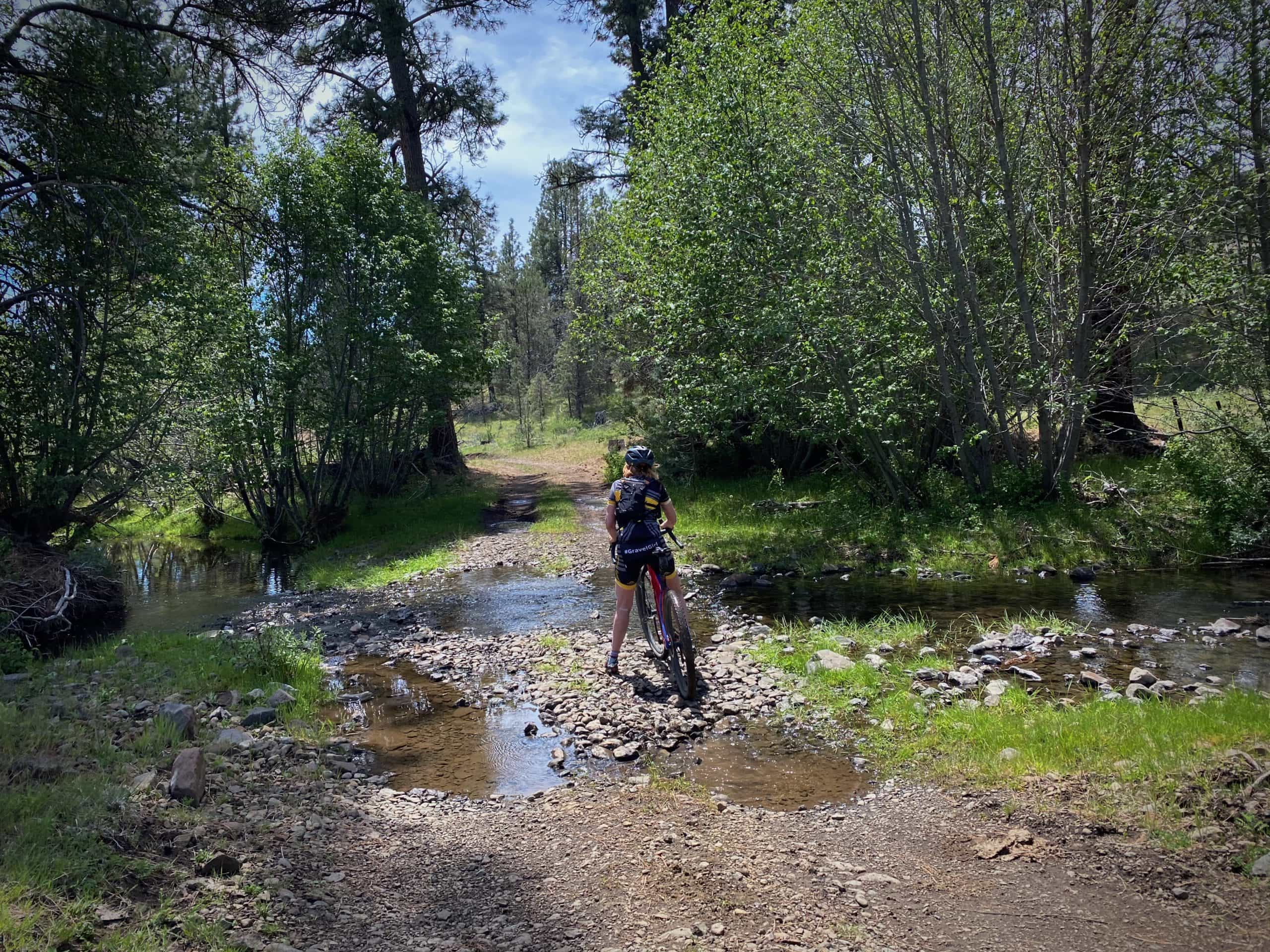 Gravel Girl crossing a stream on a primitive dirt road in the Ochoco National forest.