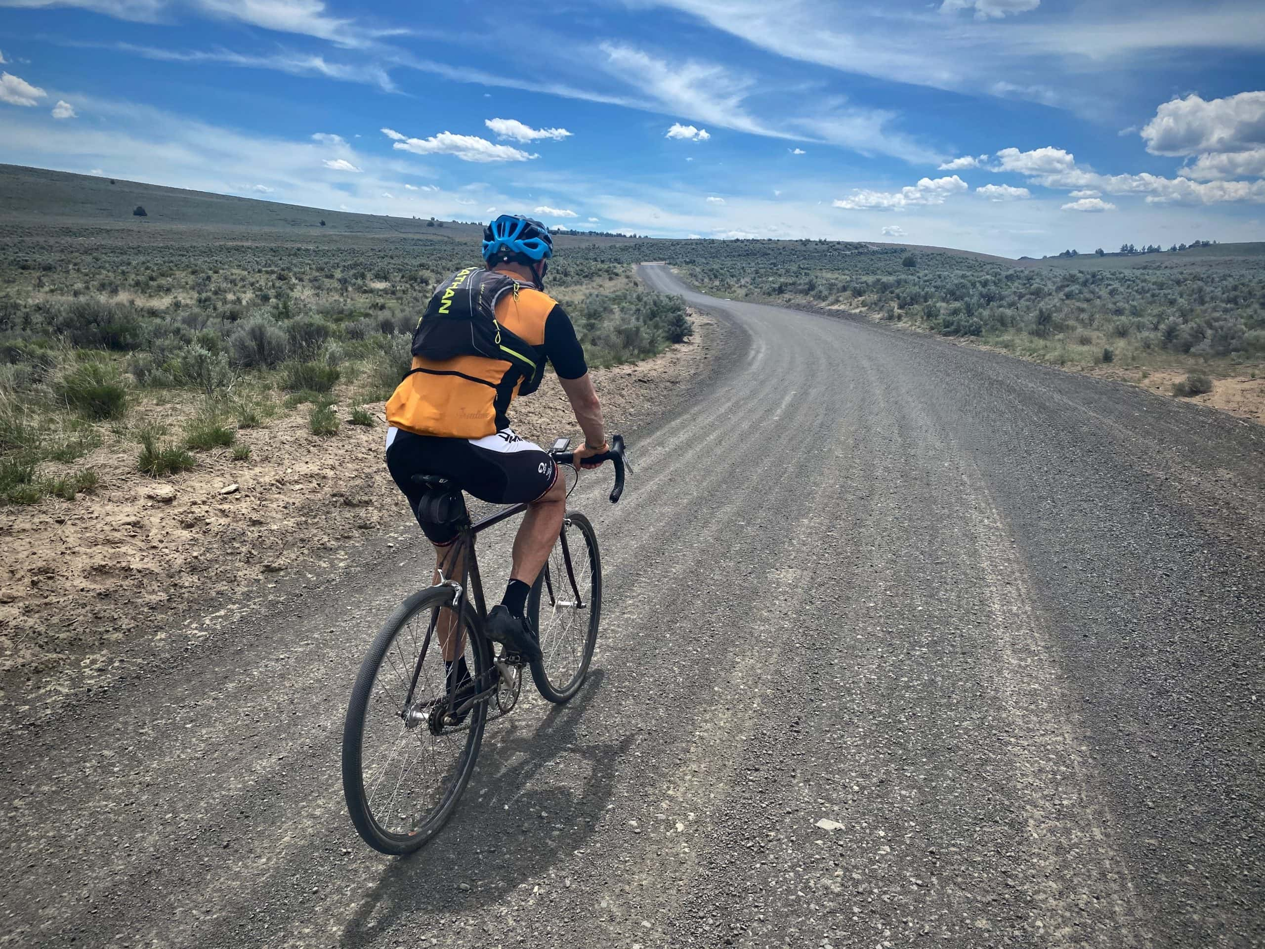 Cyclist climbing up gravel road leading to the top Sabre ridge near Paulina, OR.