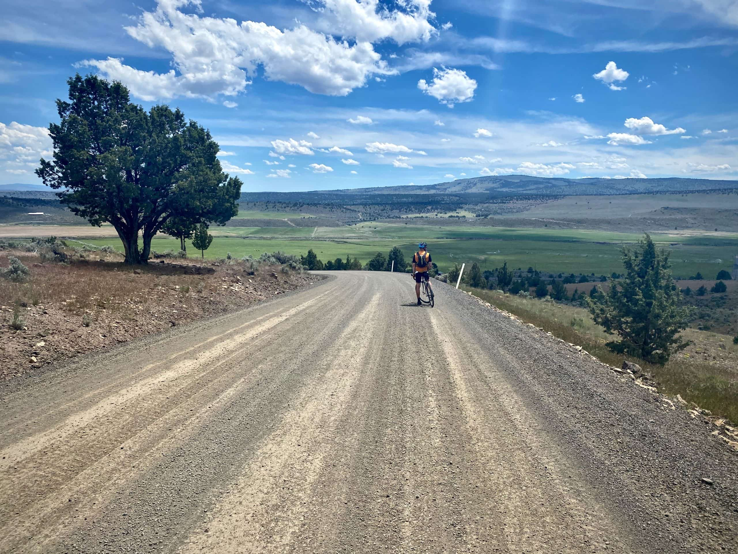 Cyclist descending gravel road into Paulina with big views.