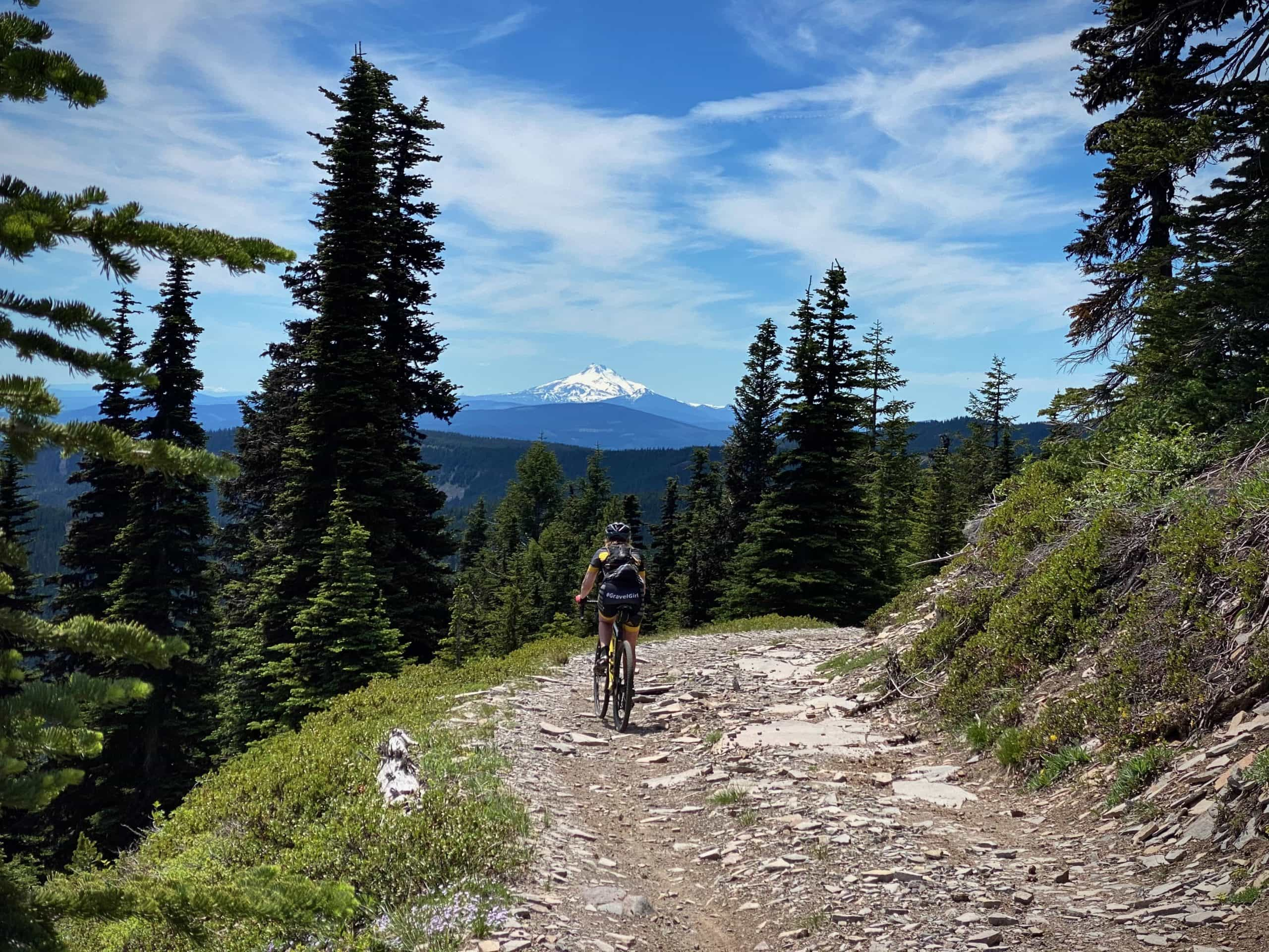 Gravel Girl riding Bennett Pass road with Mt Jefferson in the background.