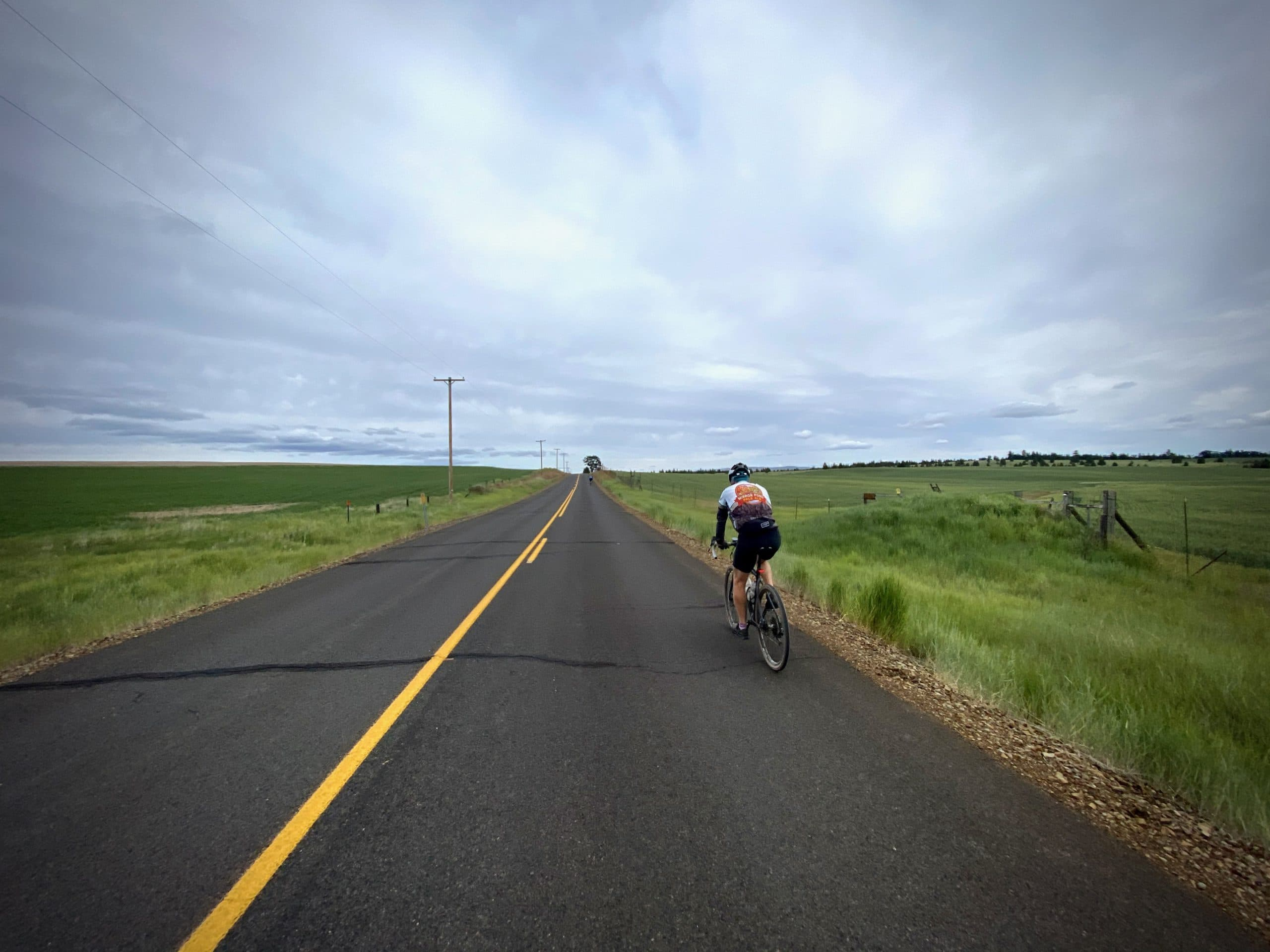 Cyclist on paved road with green fields near Friend, Oregon.