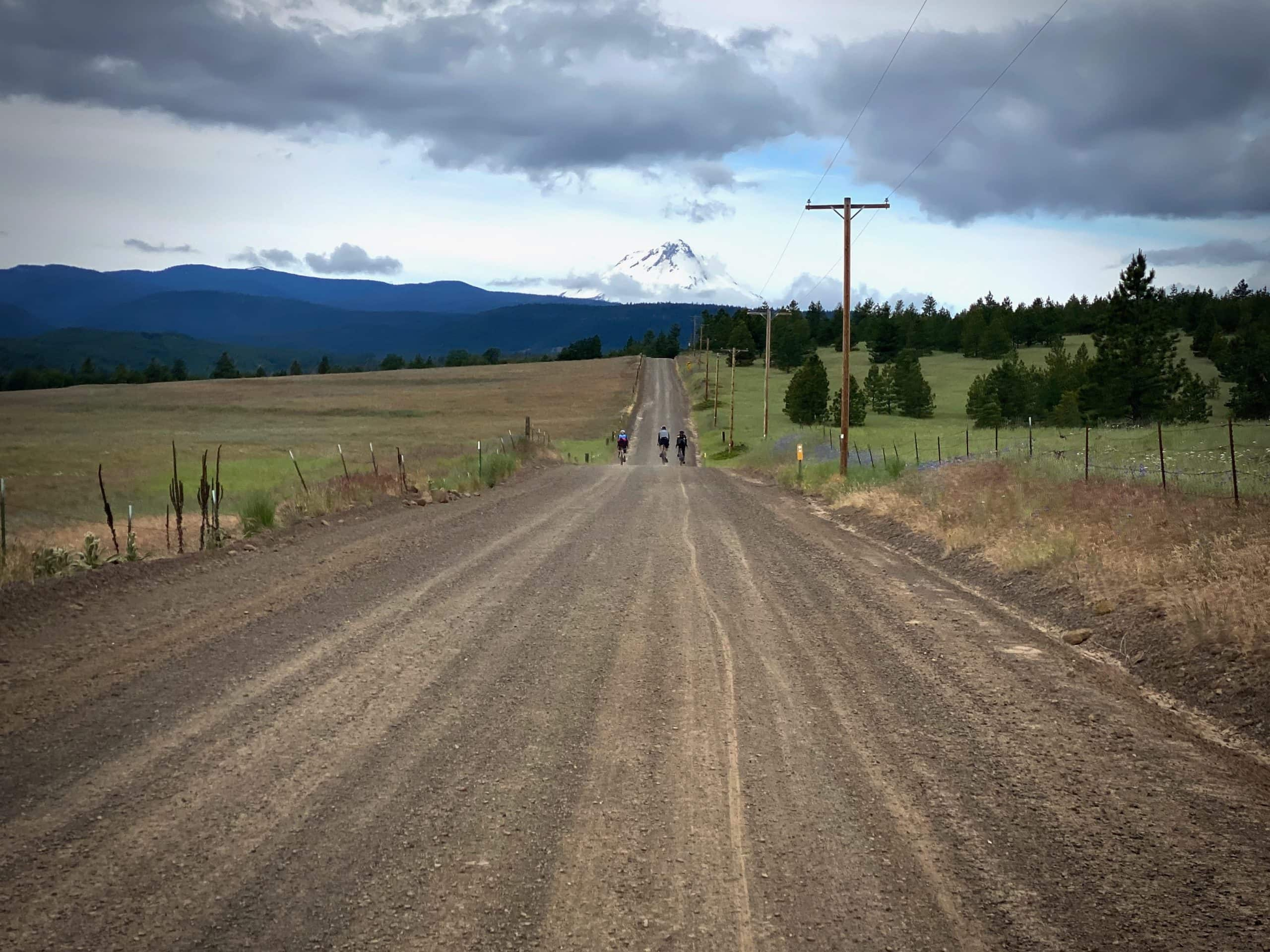 Cyclists on gravel road with Mt. Hood in the distance near Hood River, Oregon.