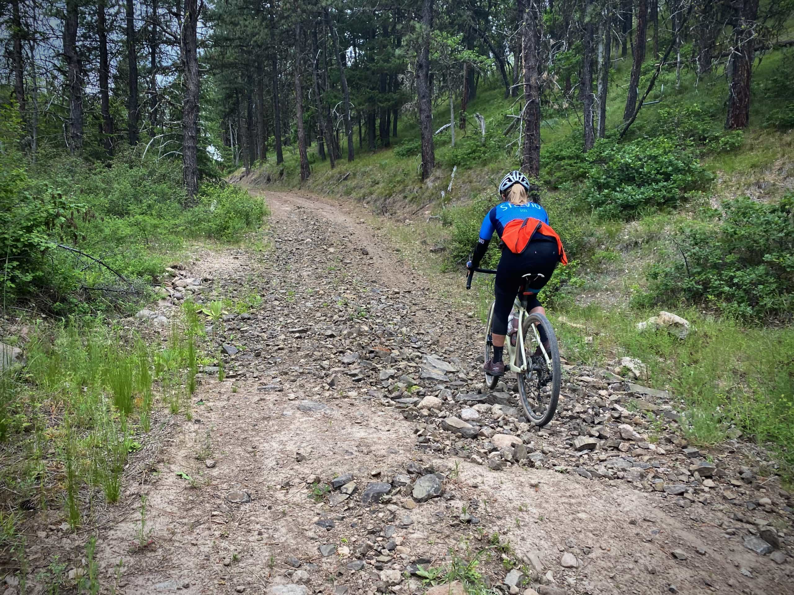 Woman cyclists making way across dry, rocky stream bed near Mt. Hood National Forest.