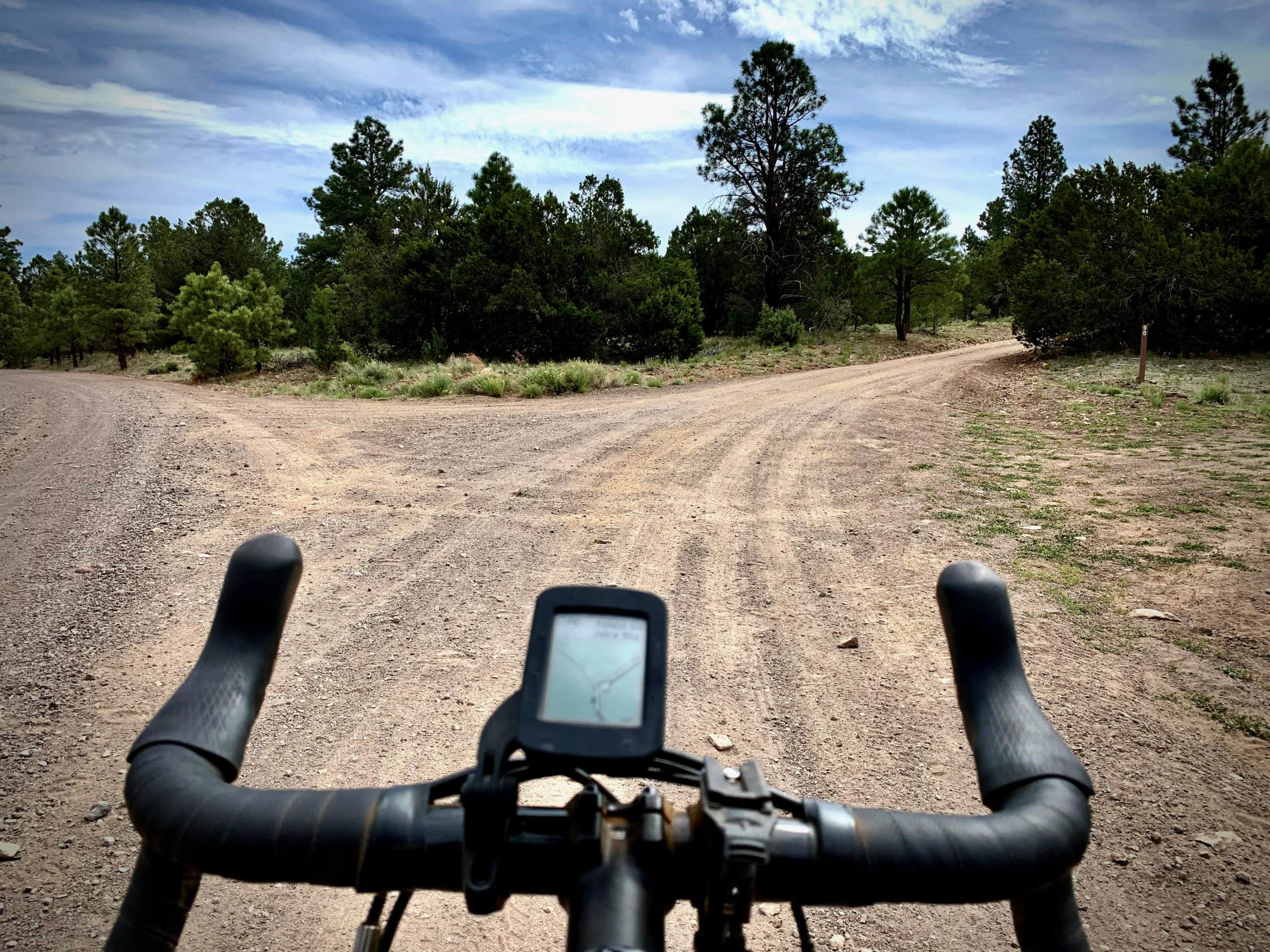 Gravel bike rider turning right onto Old 90 Forest Service road near Kendrick Mountain Wilderness.