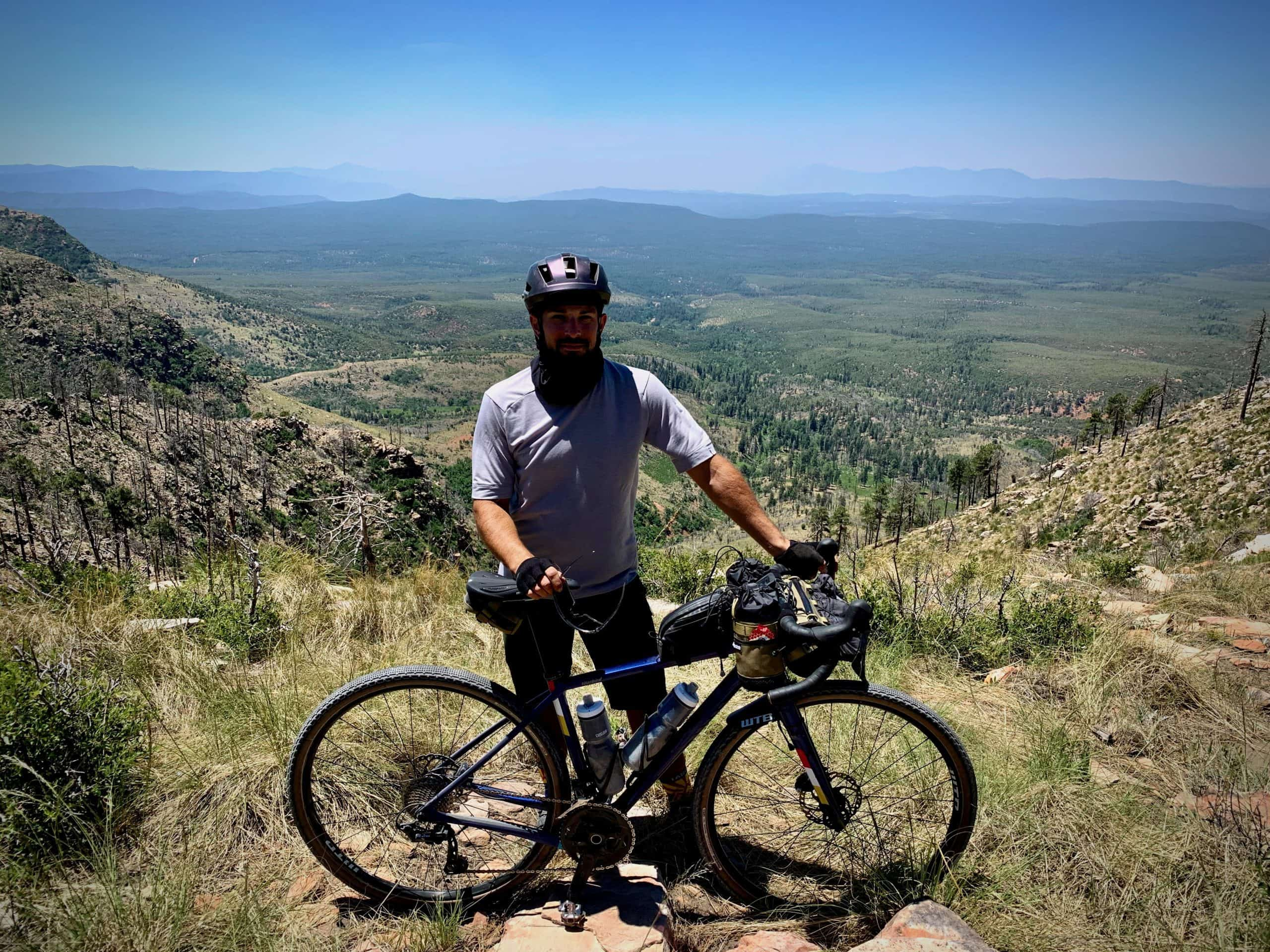 Gravel cyclists with bike and big views to the east from the Mogollon Rim in Central Arizona.