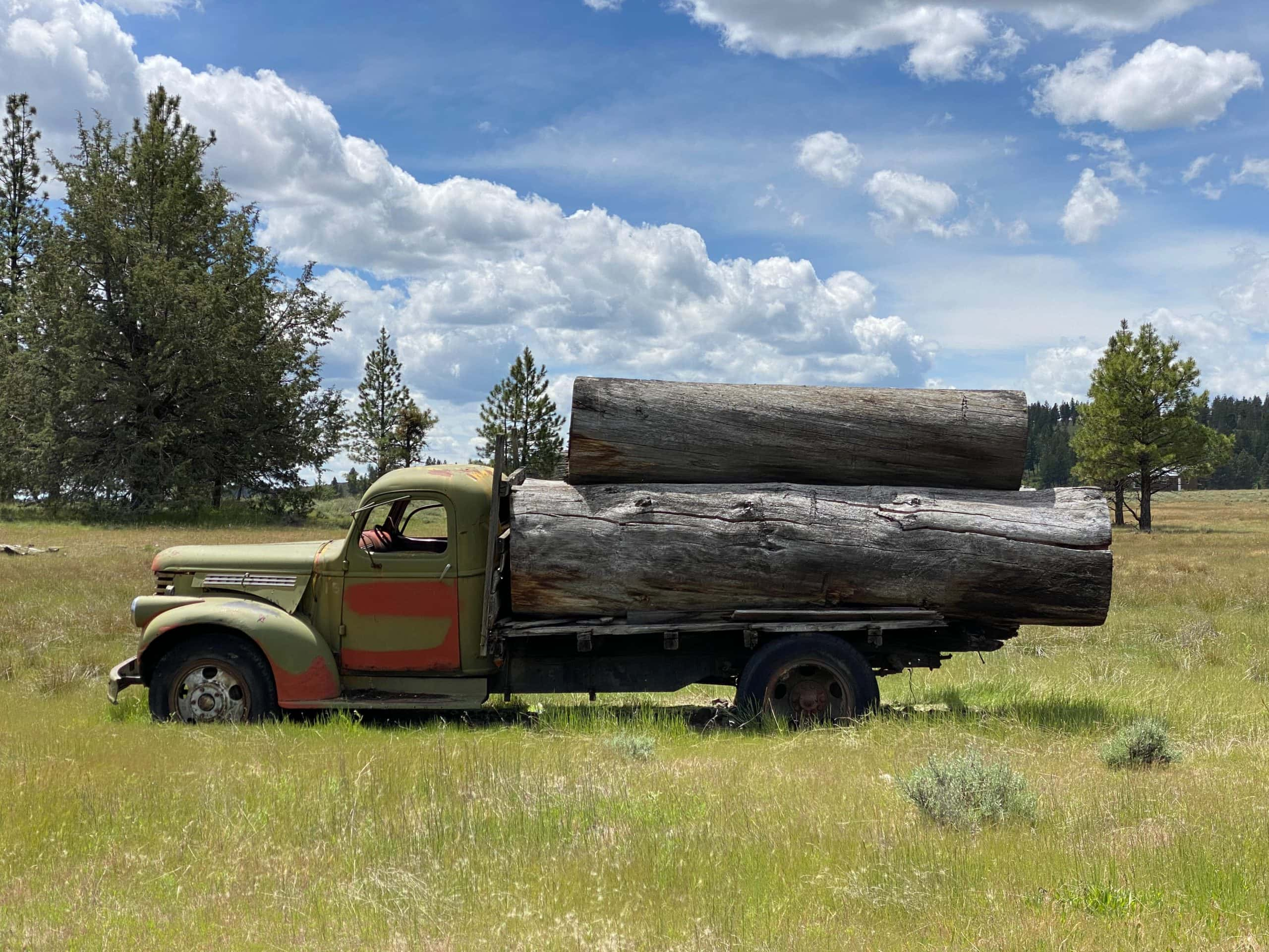 Old truck with big logs on it in meadow near Six Shooter ranch in Mitchell, Oregon.