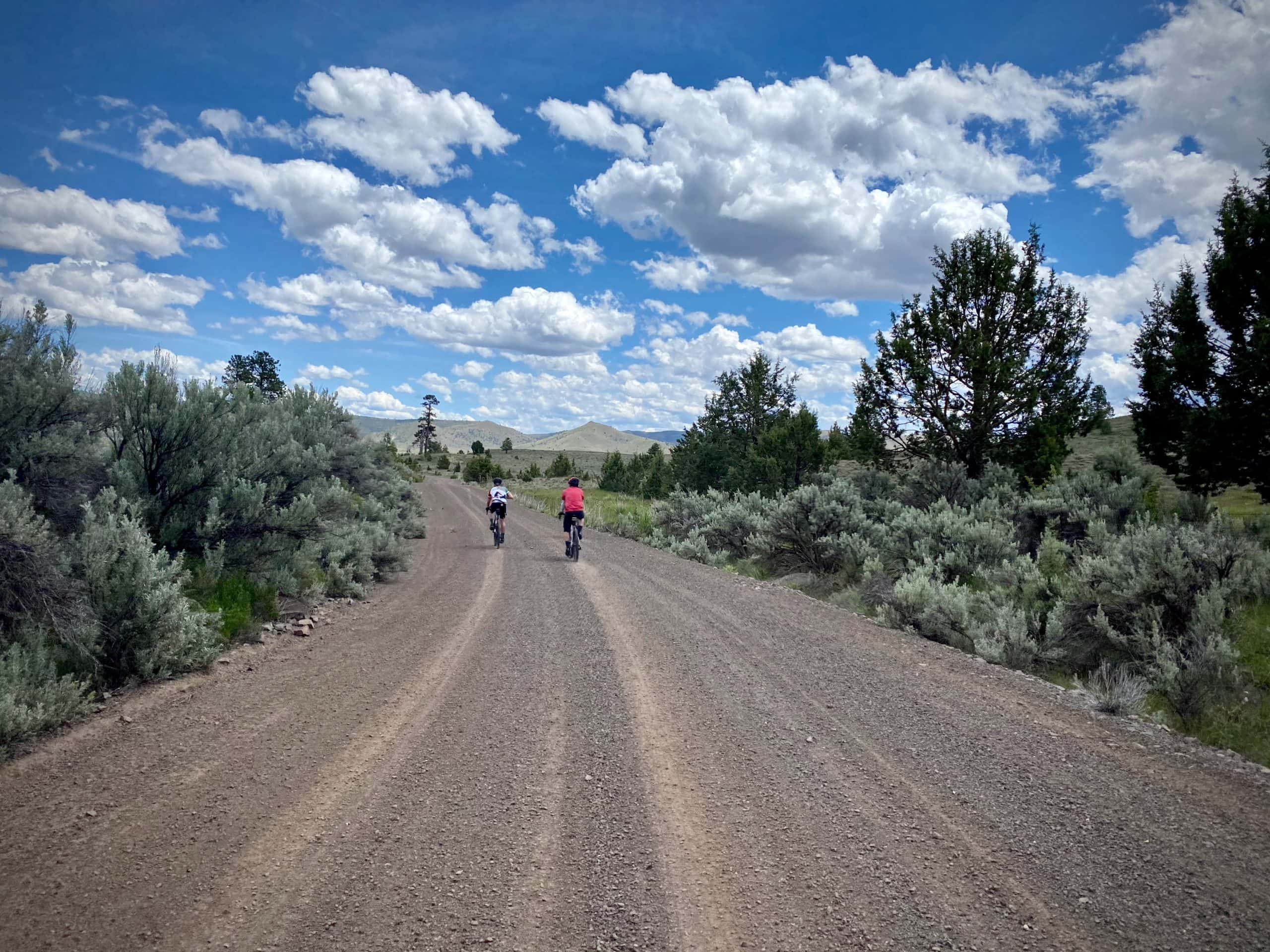 Gravel cyclists going fast on dirt road approaching Waterman Flat in Oregon.