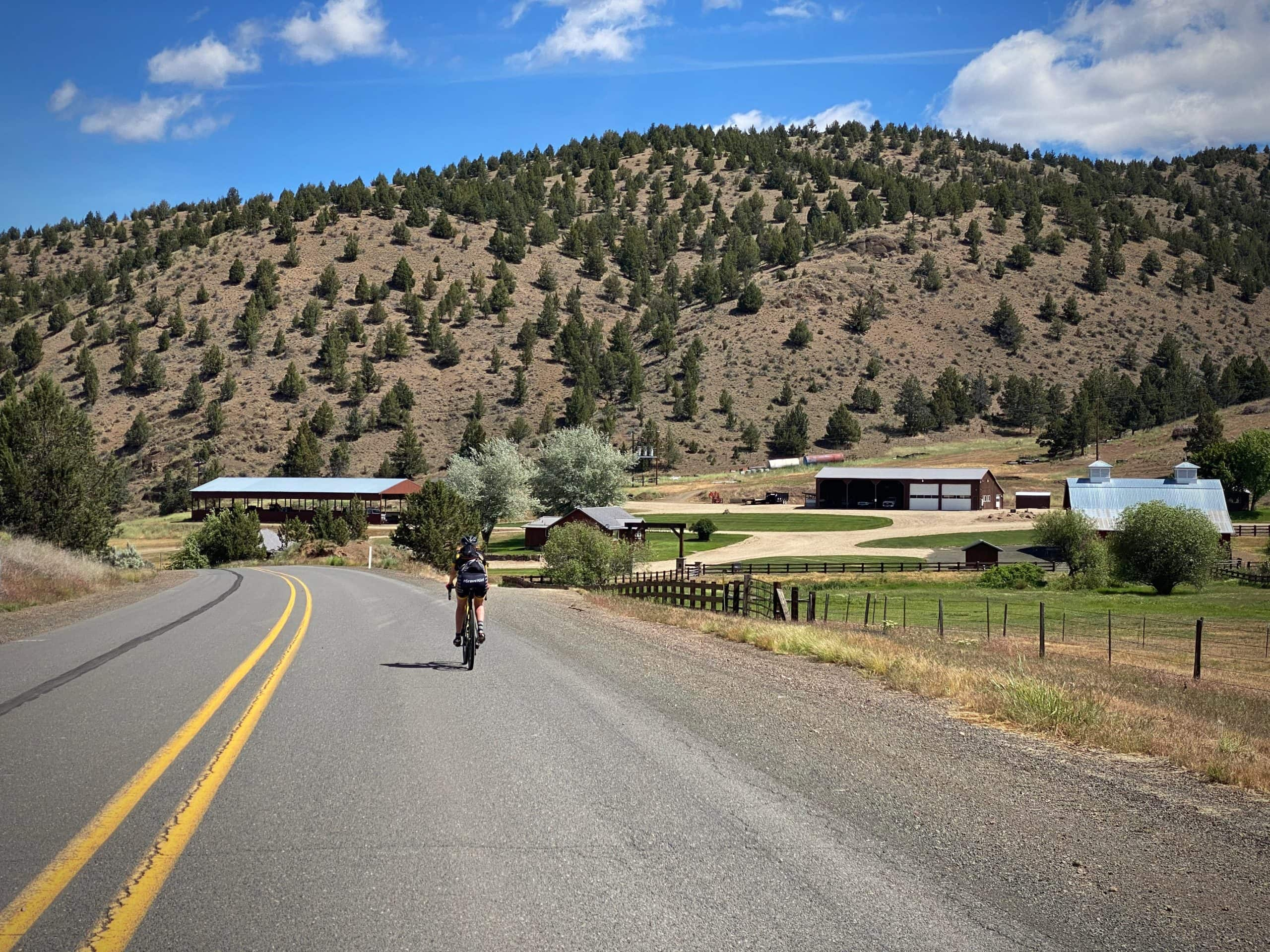 Woman cyclist riding past the Six Shooter ranch headquarters near Mitchell, OR.