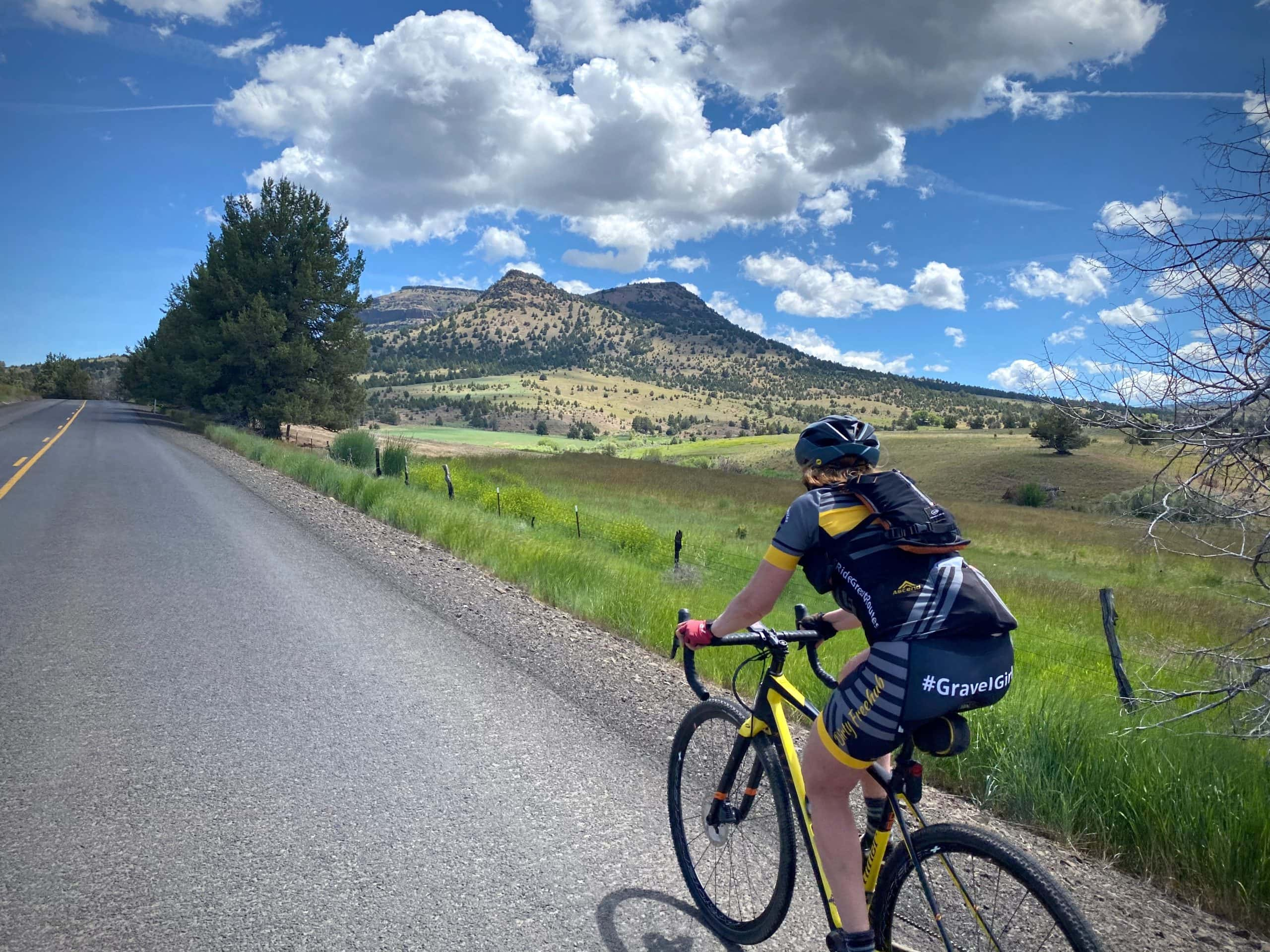 Woman cyclist climbing hill towards the ghost town of Richmond in Central Oregon.