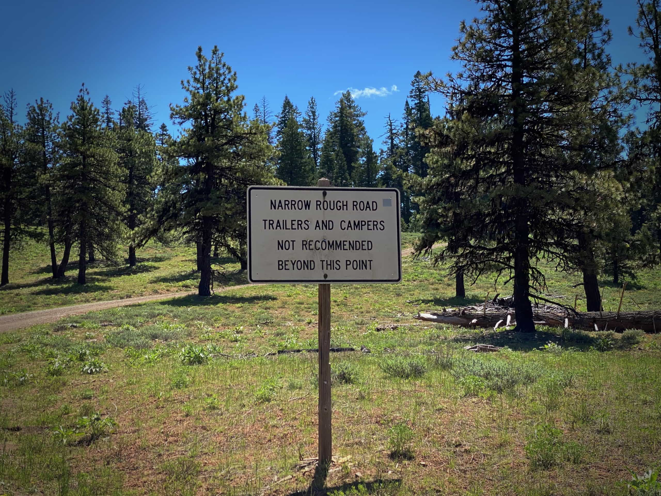 A sign along a Forest Service road advising against trailers and campers.