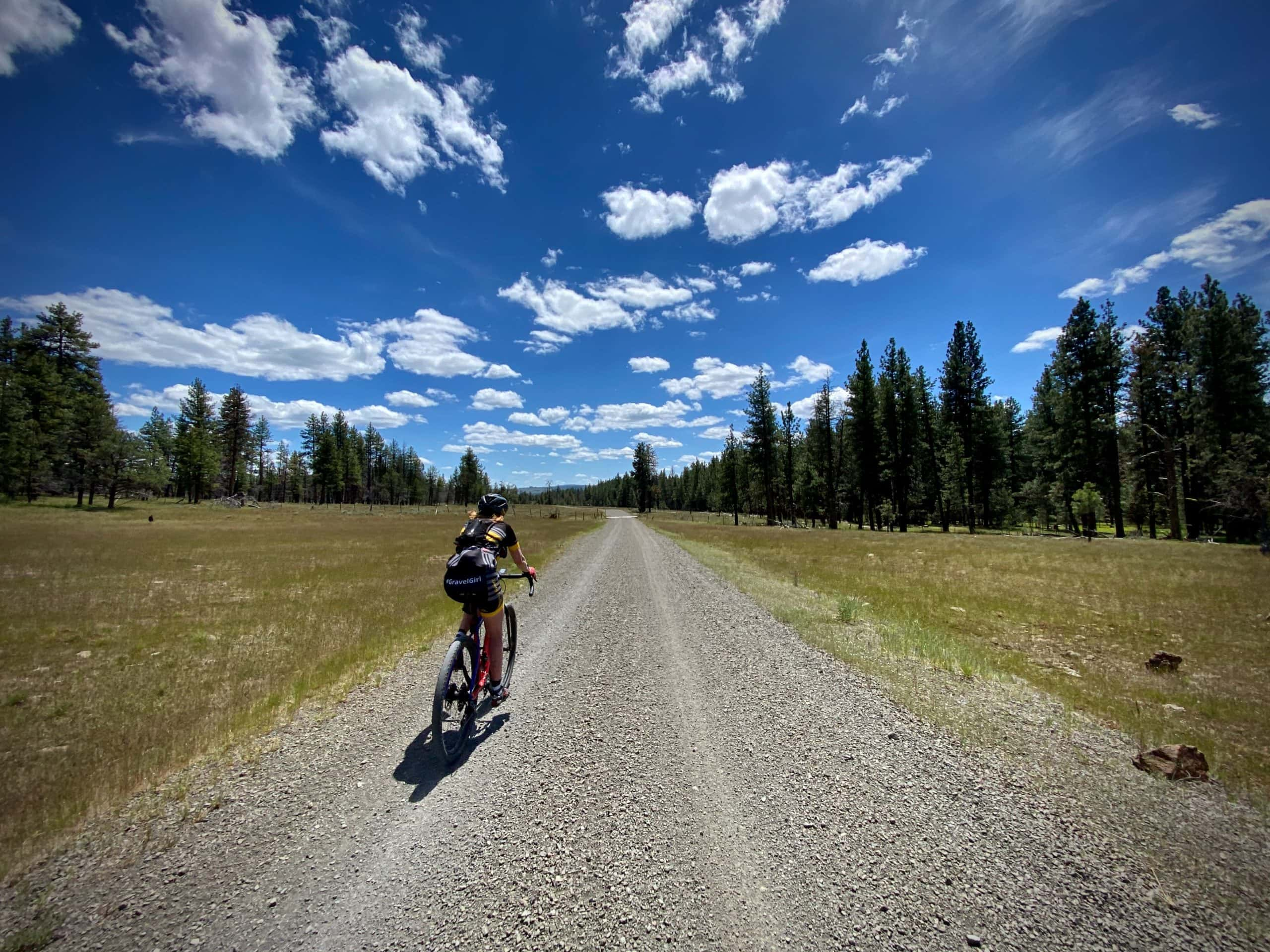 Gravel cyclist on road with open rangelands in Oregon.