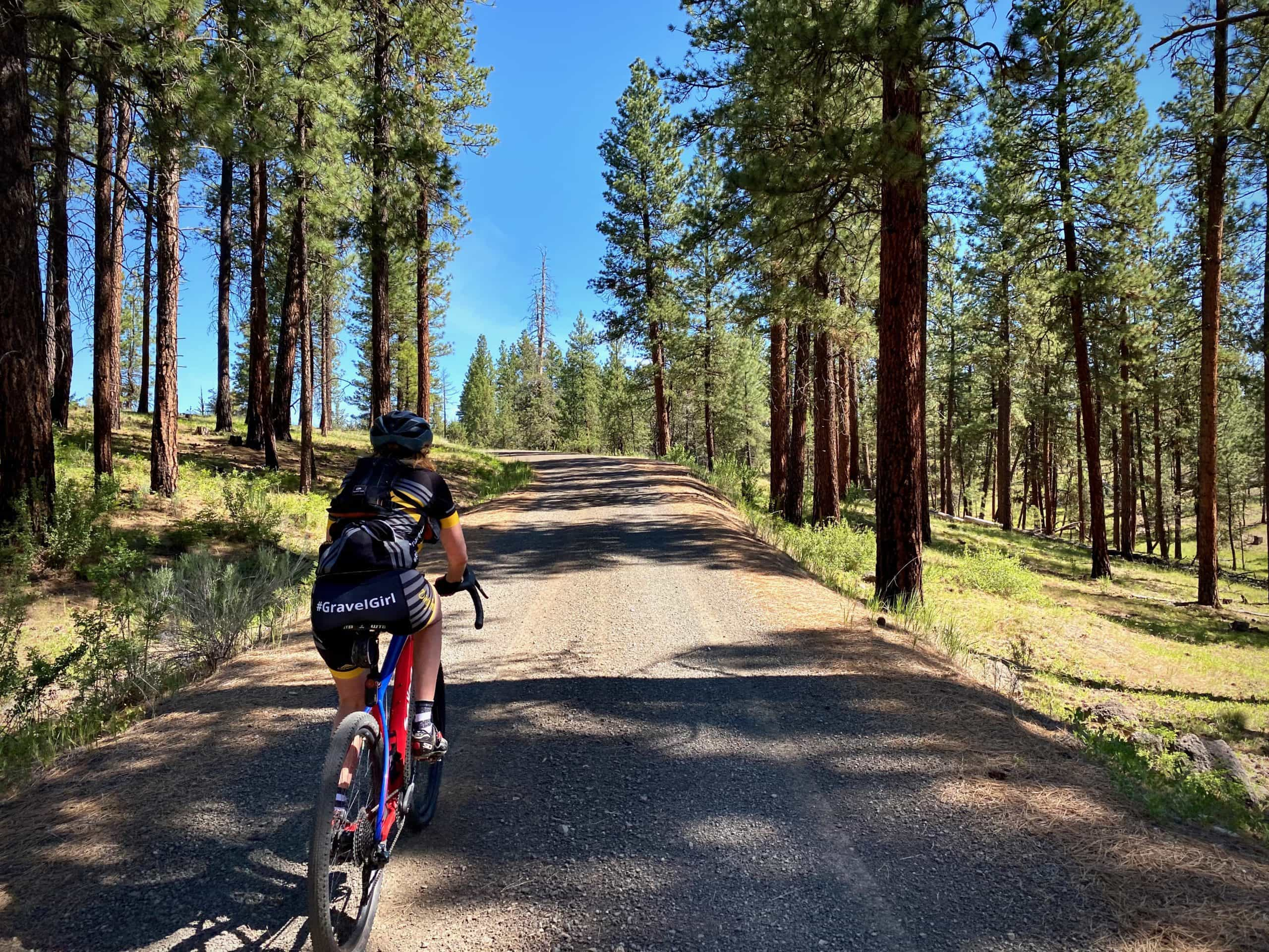 Woman gravel cyclist going uphill in Ponderosa forest in Central Oregon.