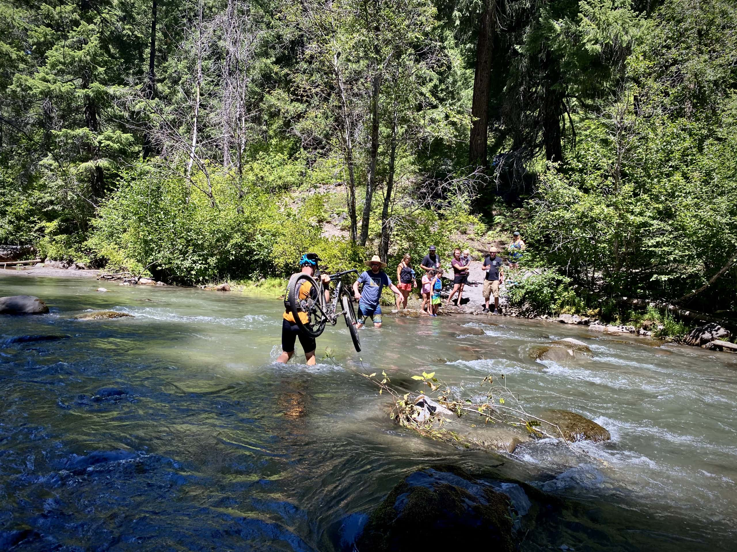 Cyclists carrying bikes across the White River near Keeps Mill campground in the Mt Hood National forest.