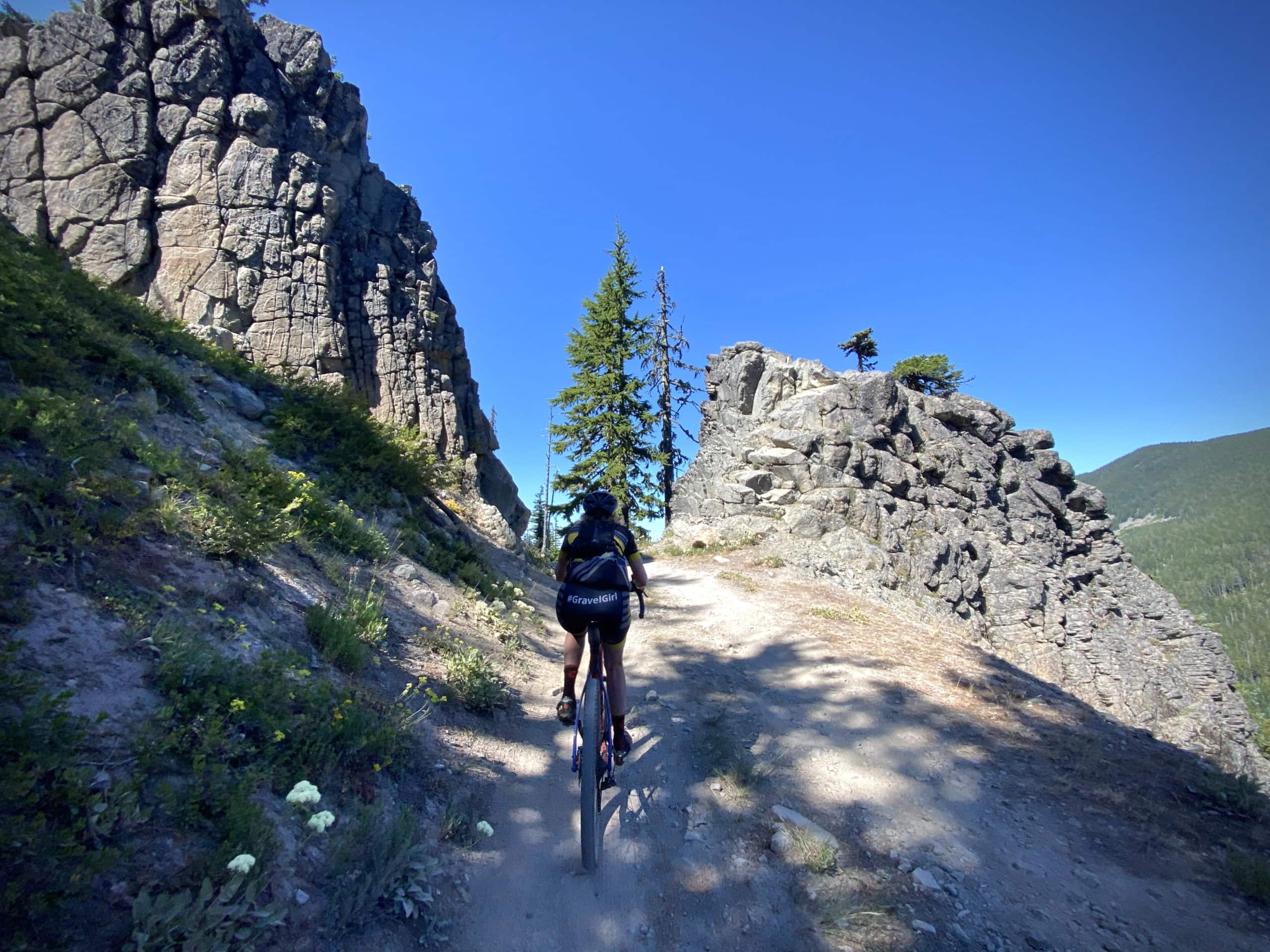 Gravel cyclist climbing rugged jeep track with a split in the rock up ahead. Mt Hood National forest.
