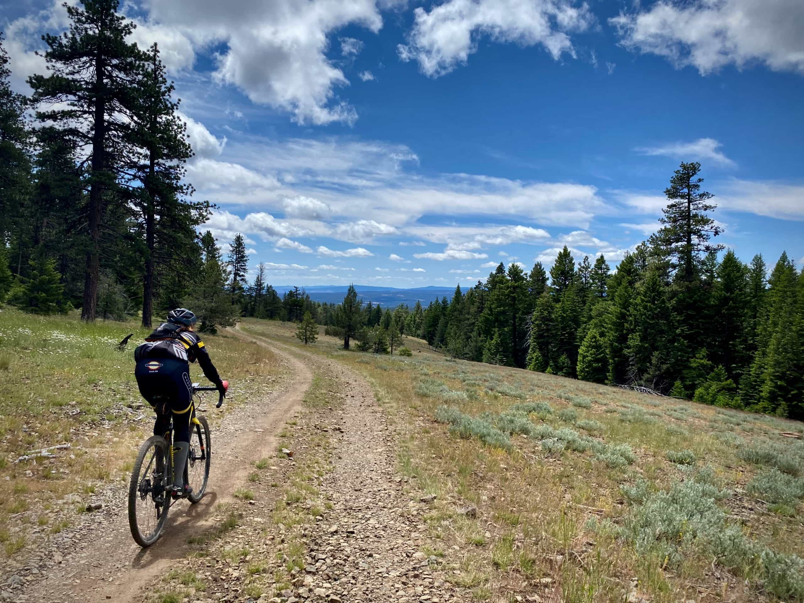 Gravel cyclist on rough, primitive track with views of Big Summit Prairie in the Ochoco Mountains.