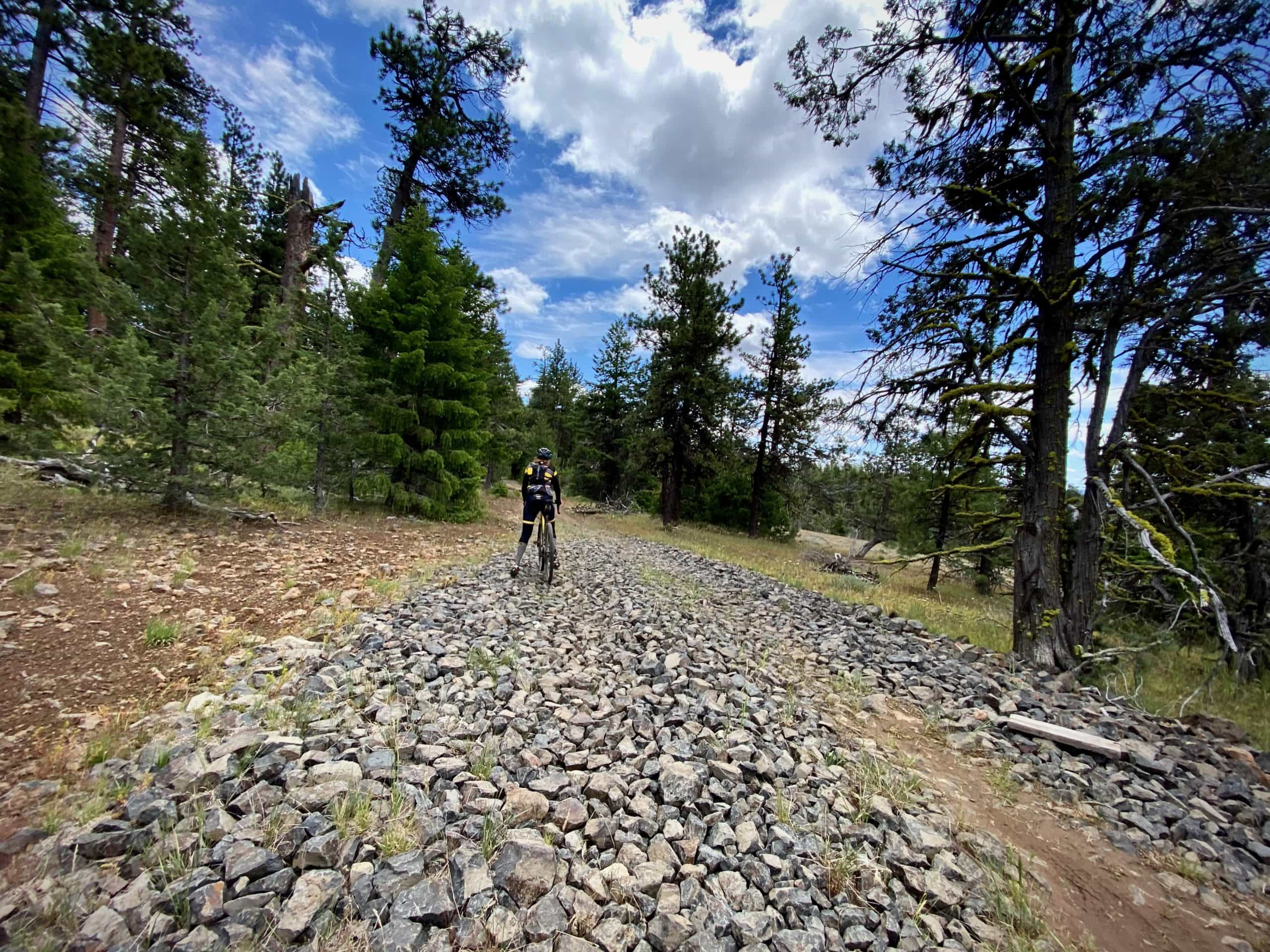 Gravel Girl riding through a rock field dumped in muddy section of forest service road.